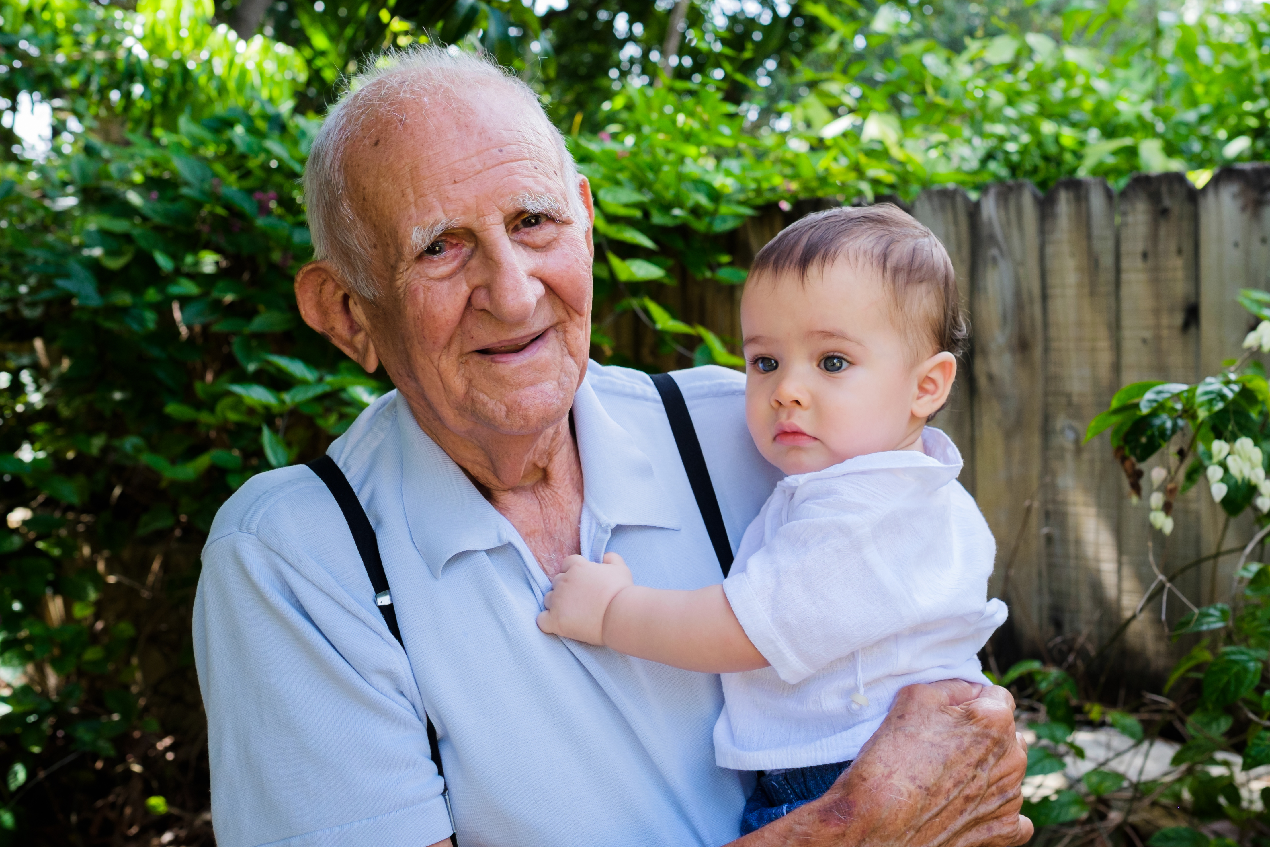 A man holds his grandson. The world's population is expected to begin to decline this century.