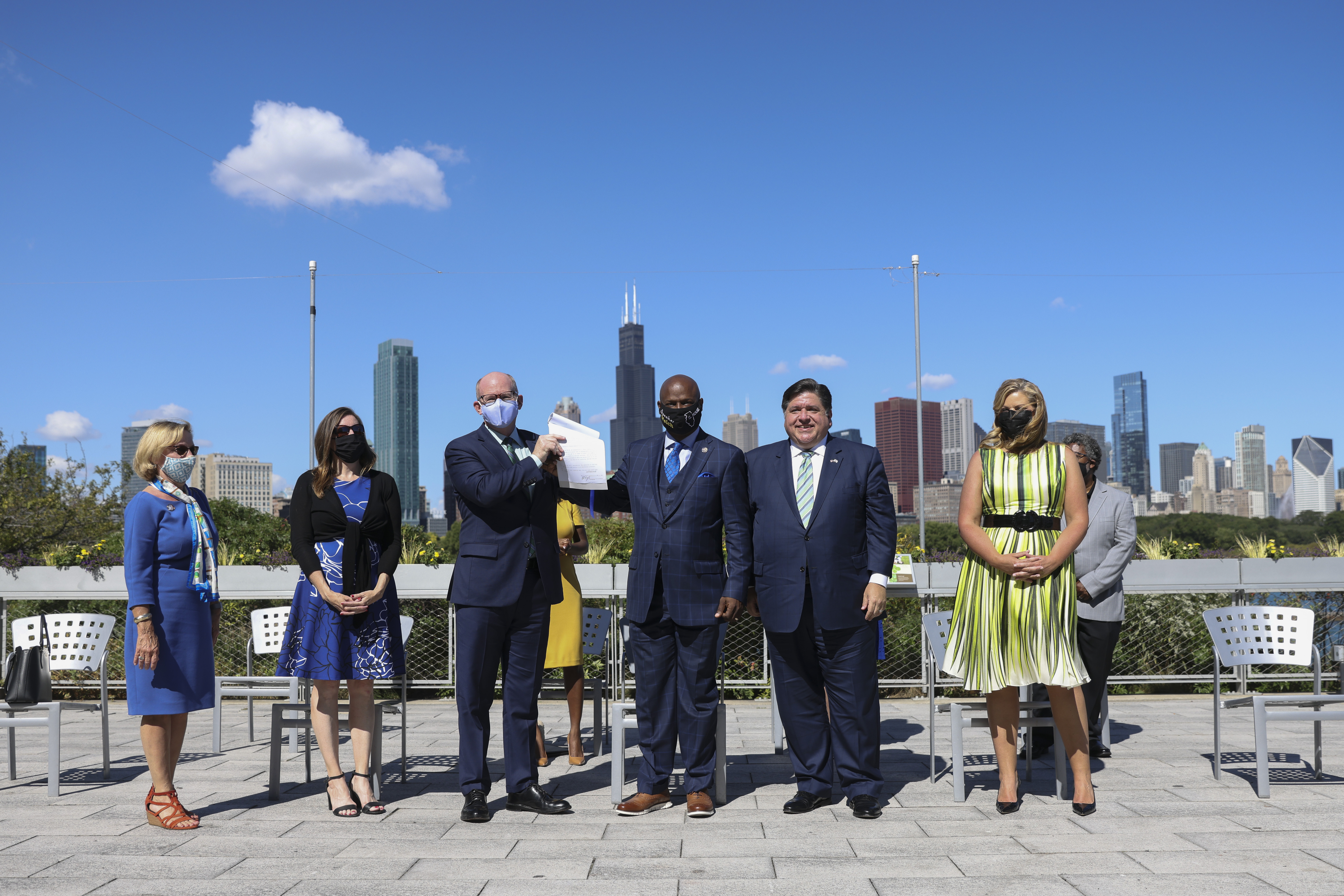 Gov. J.B. Pritzker and first lady MK Pritzker, on right, join state legislators holding up the Climate and Equitable Jobs Act at the Shedd Aquarium after the governor signed it Wednesday.