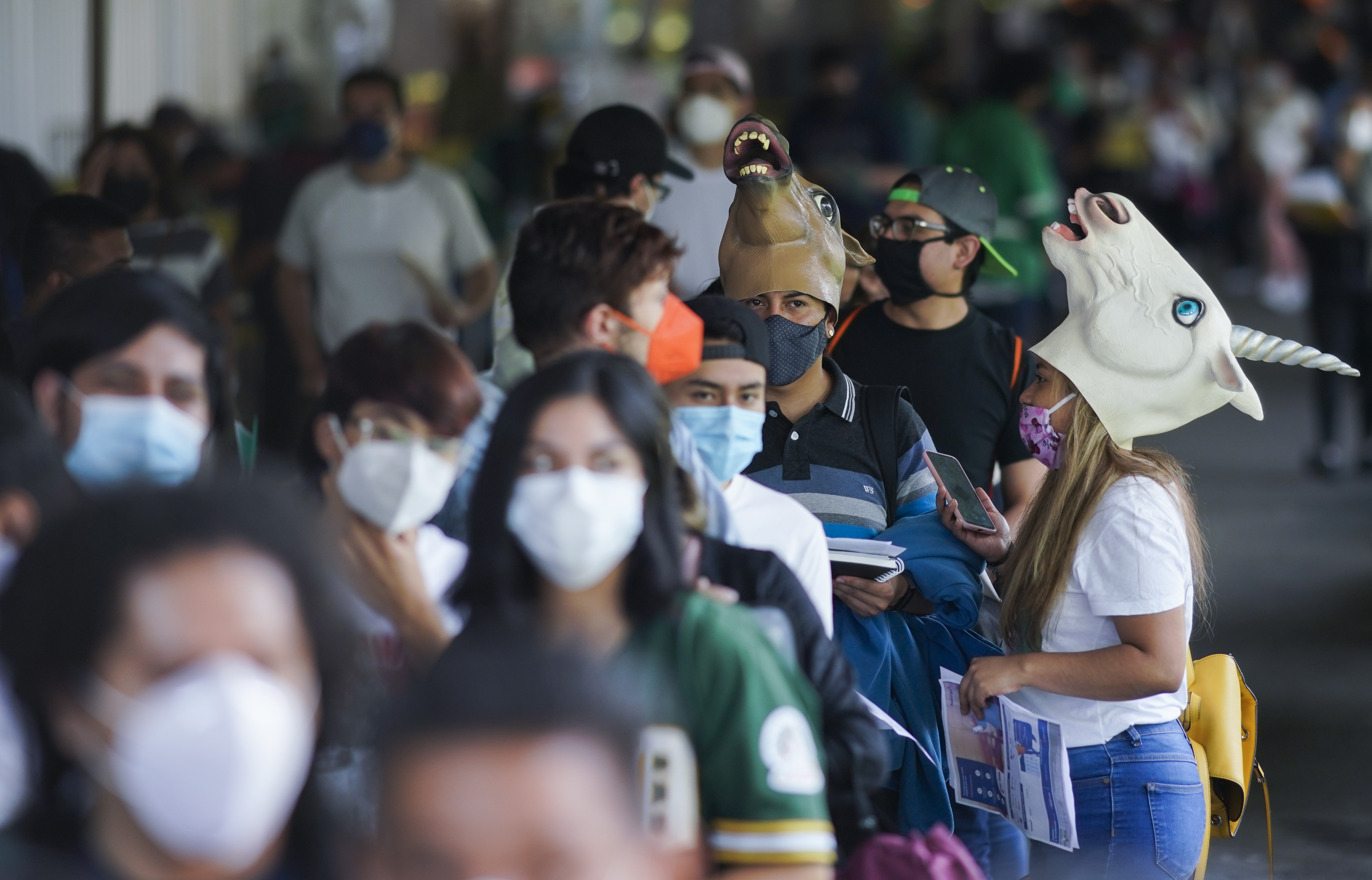 Young people, some wearing masks, wait for COVID-19 shots during a vaccination drive for people between the ages of 18 and 29 in Mexico City. The capital's south side borough of Xochimilco is encouraging young residents to dress up in costumes and compete for prizes if they come for their first COVID-19 vaccine dose.