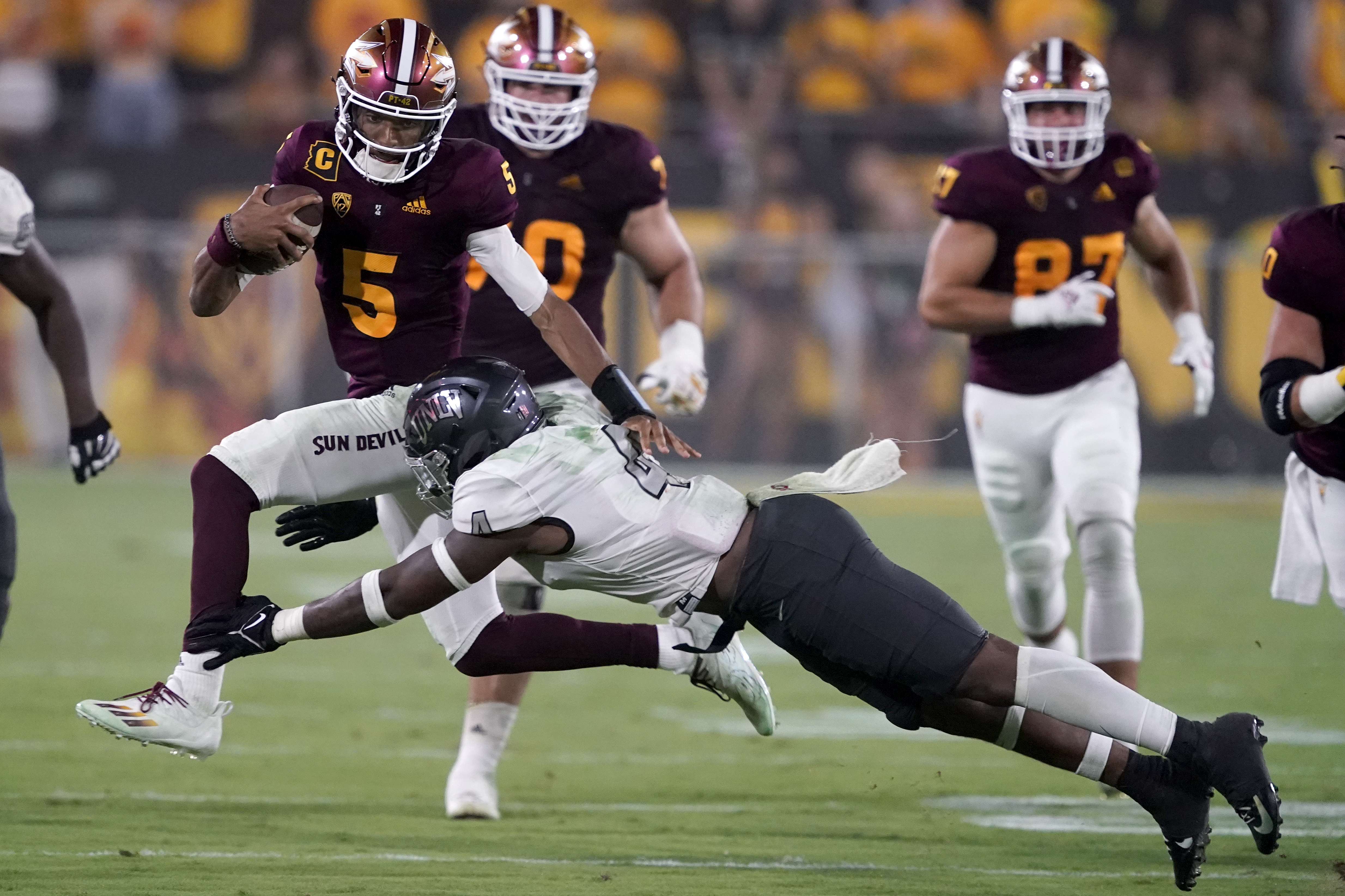 Arizona State quarterback Jayden Daniels avoids the tackle of UNLV player during game Sept. 11, 2021, in Tempe, Ariz.