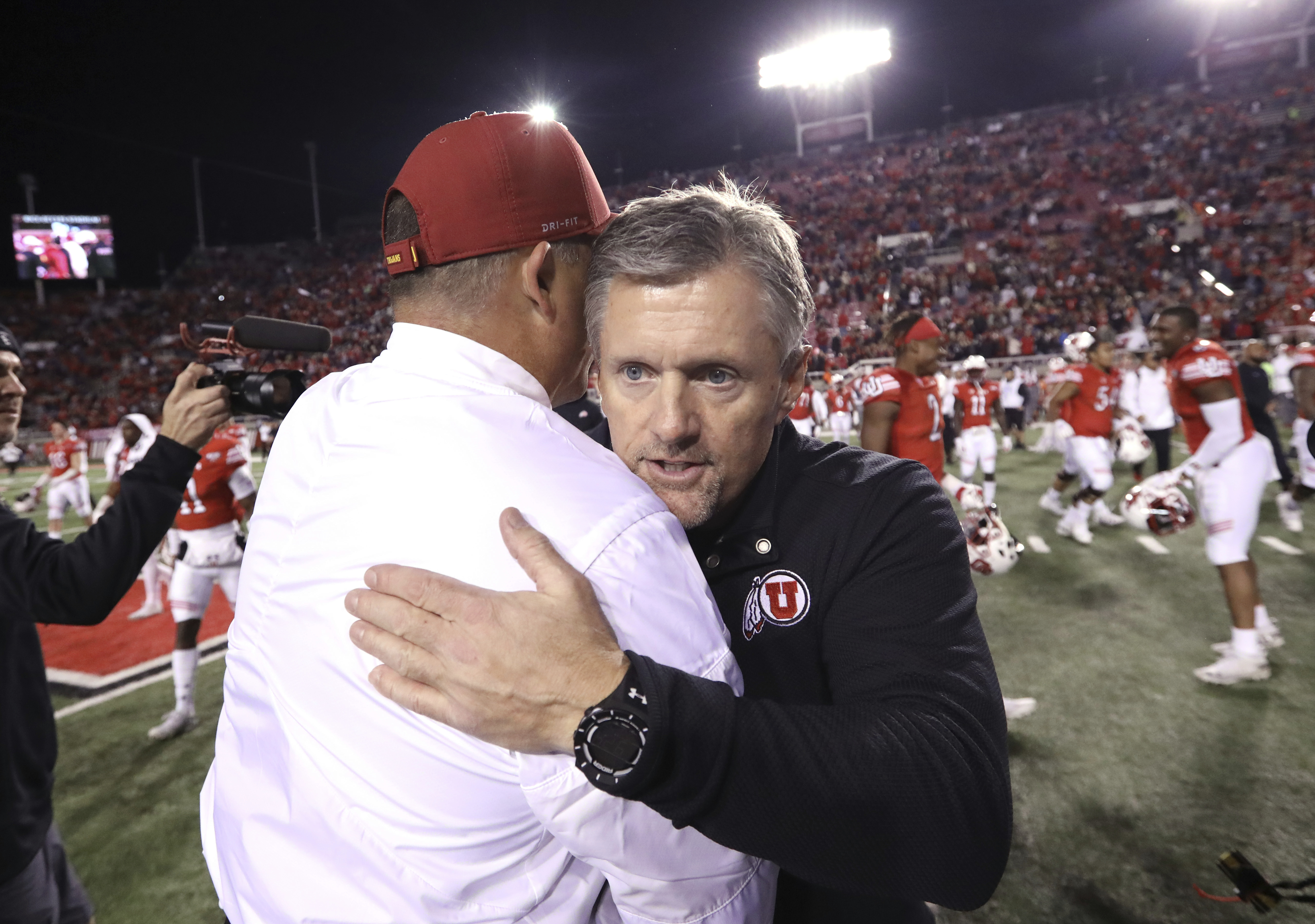 Utah head coach Kyle Whittingham, right, shakes hands with USC head coach Clay Helton following their game, Oct. 20, 2018.