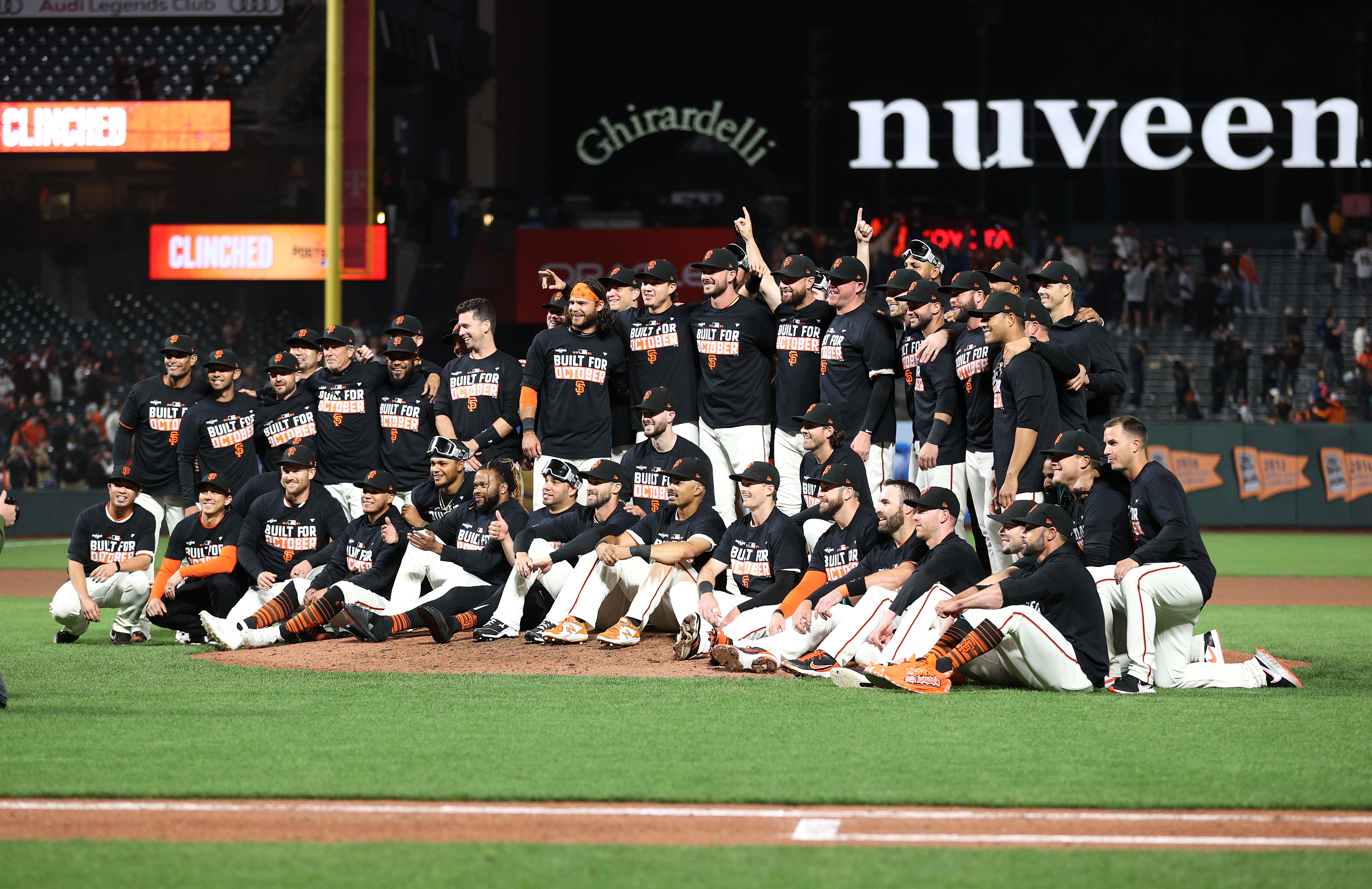 The San Francisco Giants pose for a team photo on the field after they clinched a playoff birth by beating the San Diego Padres at Oracle Park on September 13, 2021 in San Francisco, California.