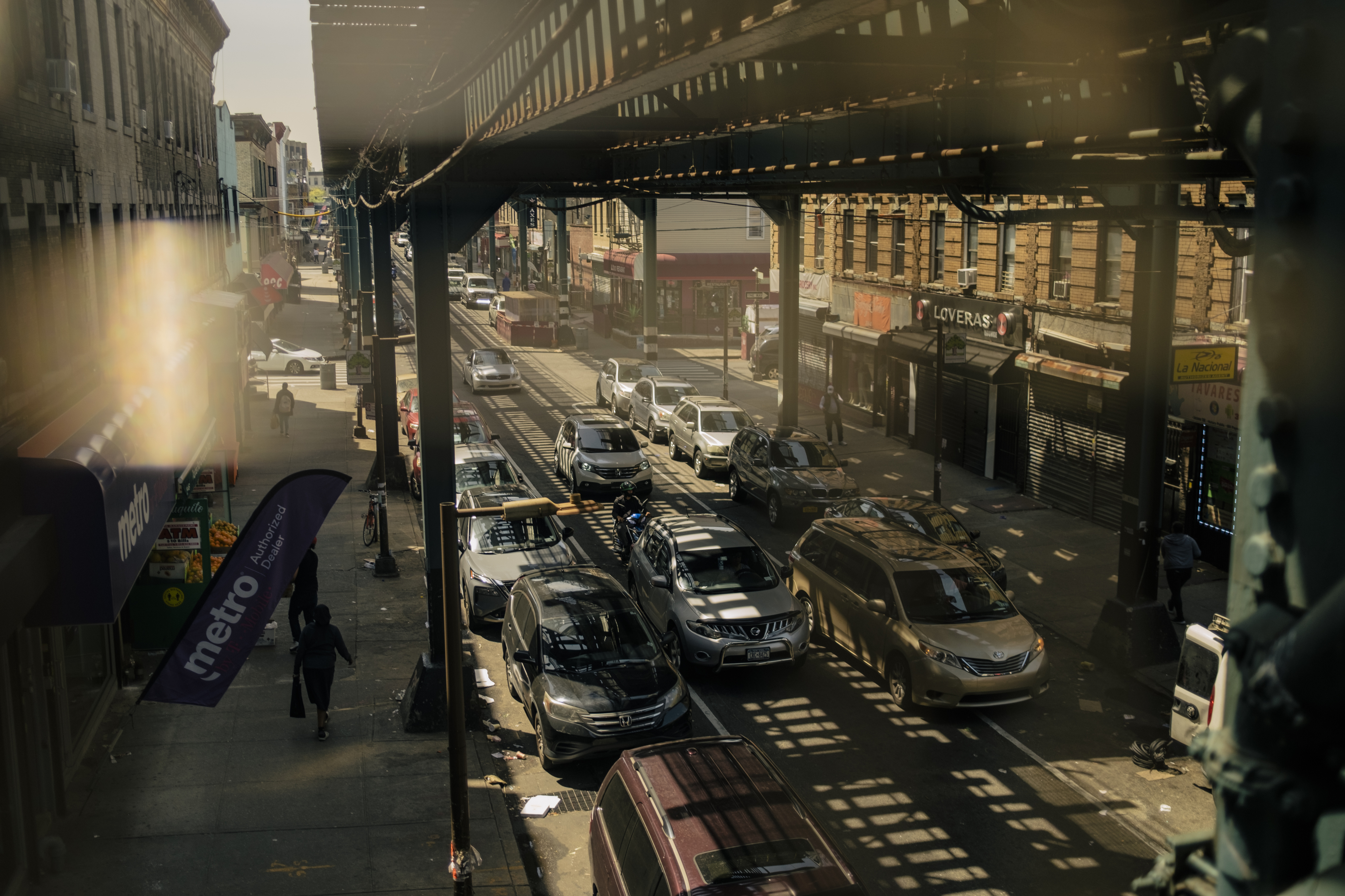A bustling street in Cypress Hills, Brooklyn, with traffic moving under a subway track and shadows lining the street.
