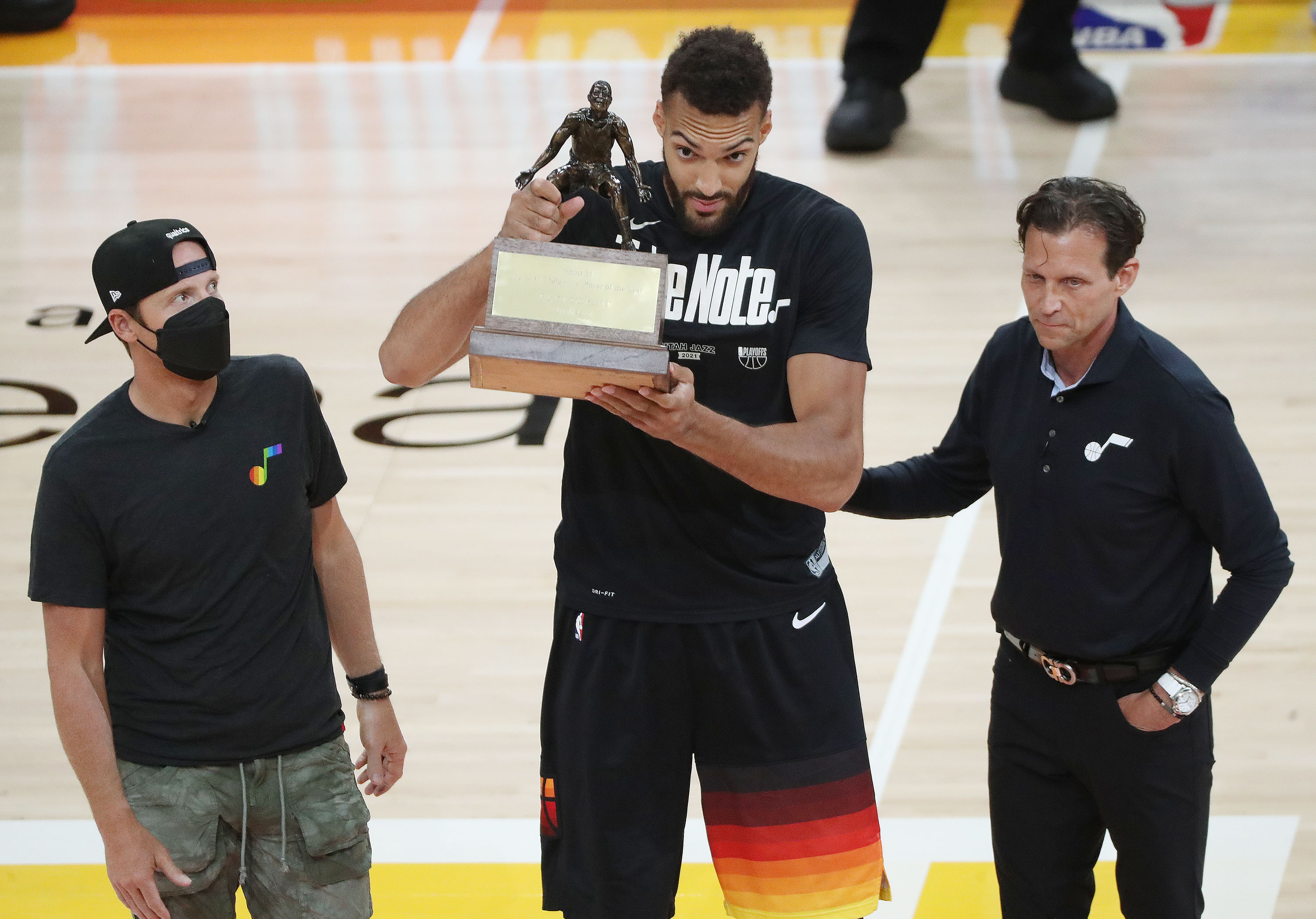 Utah Jazz center Rudy Gobert (27) receives his Defensive player of the Year trophy with Jazz coach Quin Synder and owner Ryan Smith prior to the game in Salt Lake City on Thursday, June 10, 2021. The Jazz won 117-111.