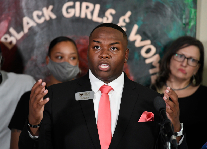 Denver school board member Tay Anderson gestures while speaking at a press conference. He is wearing a black suit and salmon colored tie. Supporters are standing behind him.