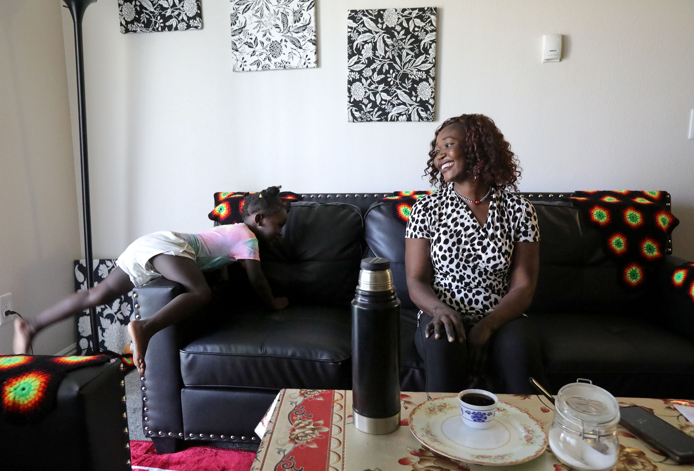 Siyanna Inna climbs on the couch as her mother, Tabitha Kwayge, a Sudanese refugee, laughs at their apartment in Midvale, Utah.
