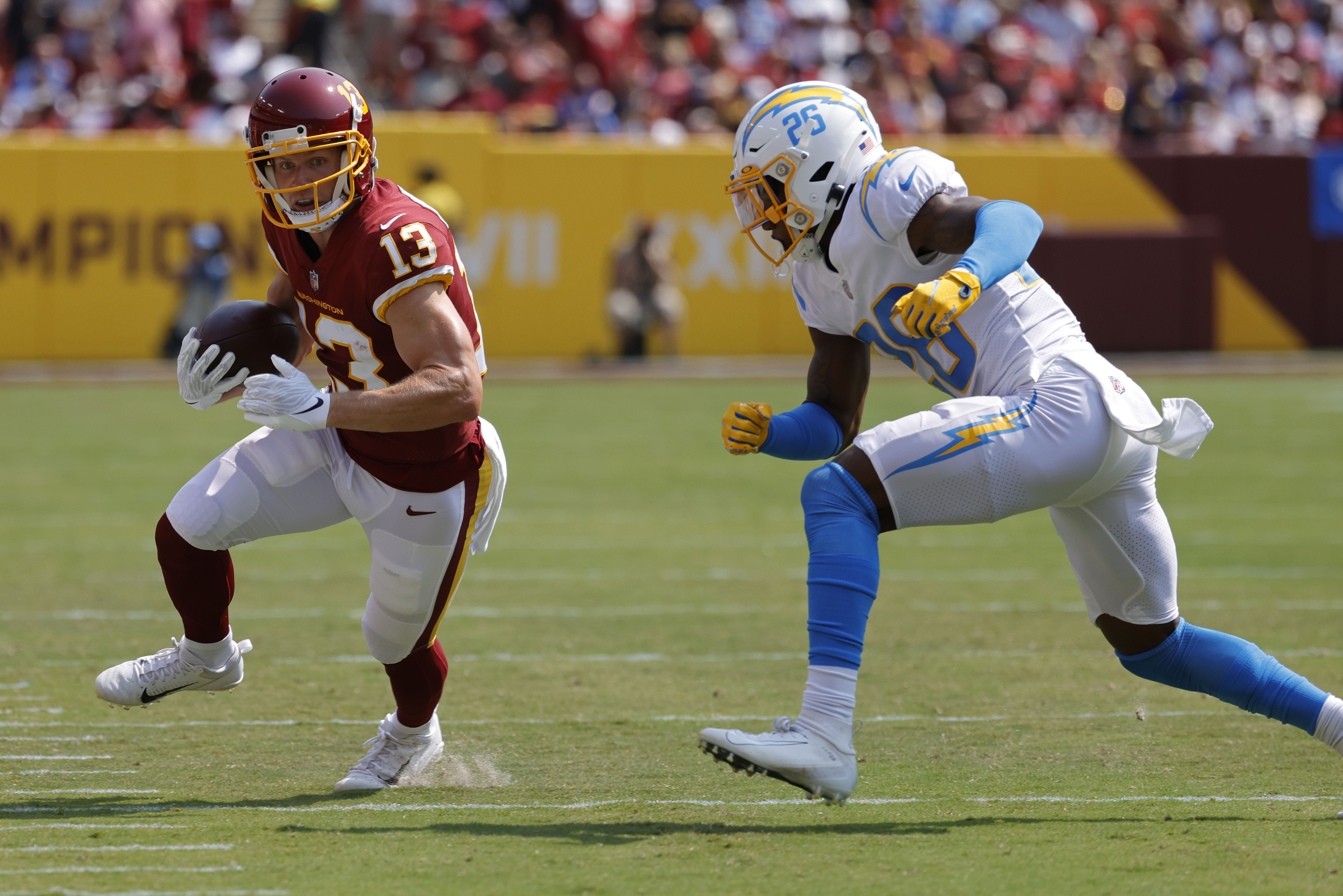 Washington Football Team wide receiver Adam Humphries (13) runs with the ball as Los Angeles Chargers cornerback Chris Harris Jr. (25) chases in the first quarter at FedExField. Mandatory Credit: Geoff Burke