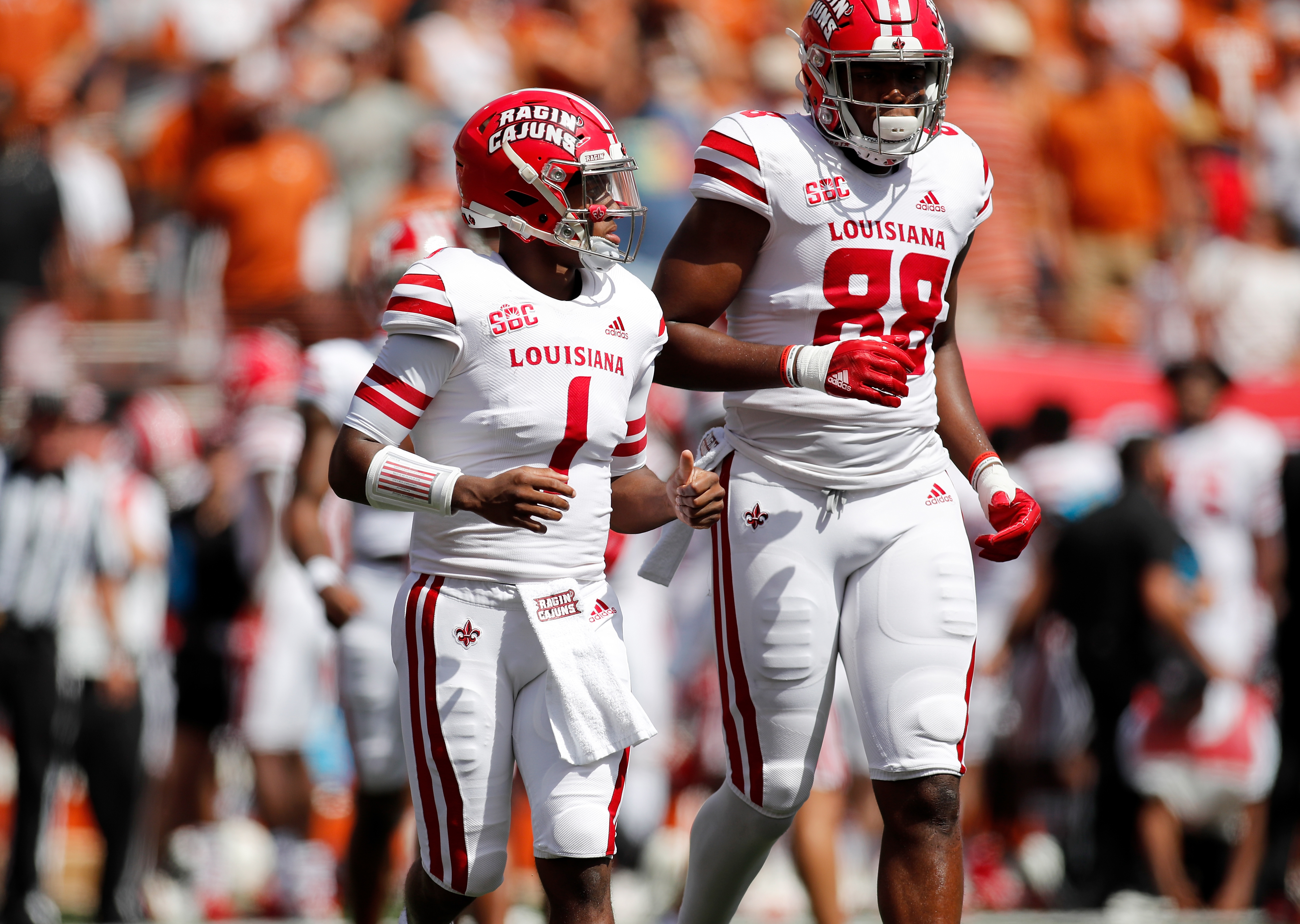 Levi Lewis of the Louisiana Ragin' Cajuns and Johnny Lumpkin take the field in the first quarter against the Texas Longhorns at Darrell K Royal-Texas Memorial Stadium on September 04, 2021 in Austin, Texas.