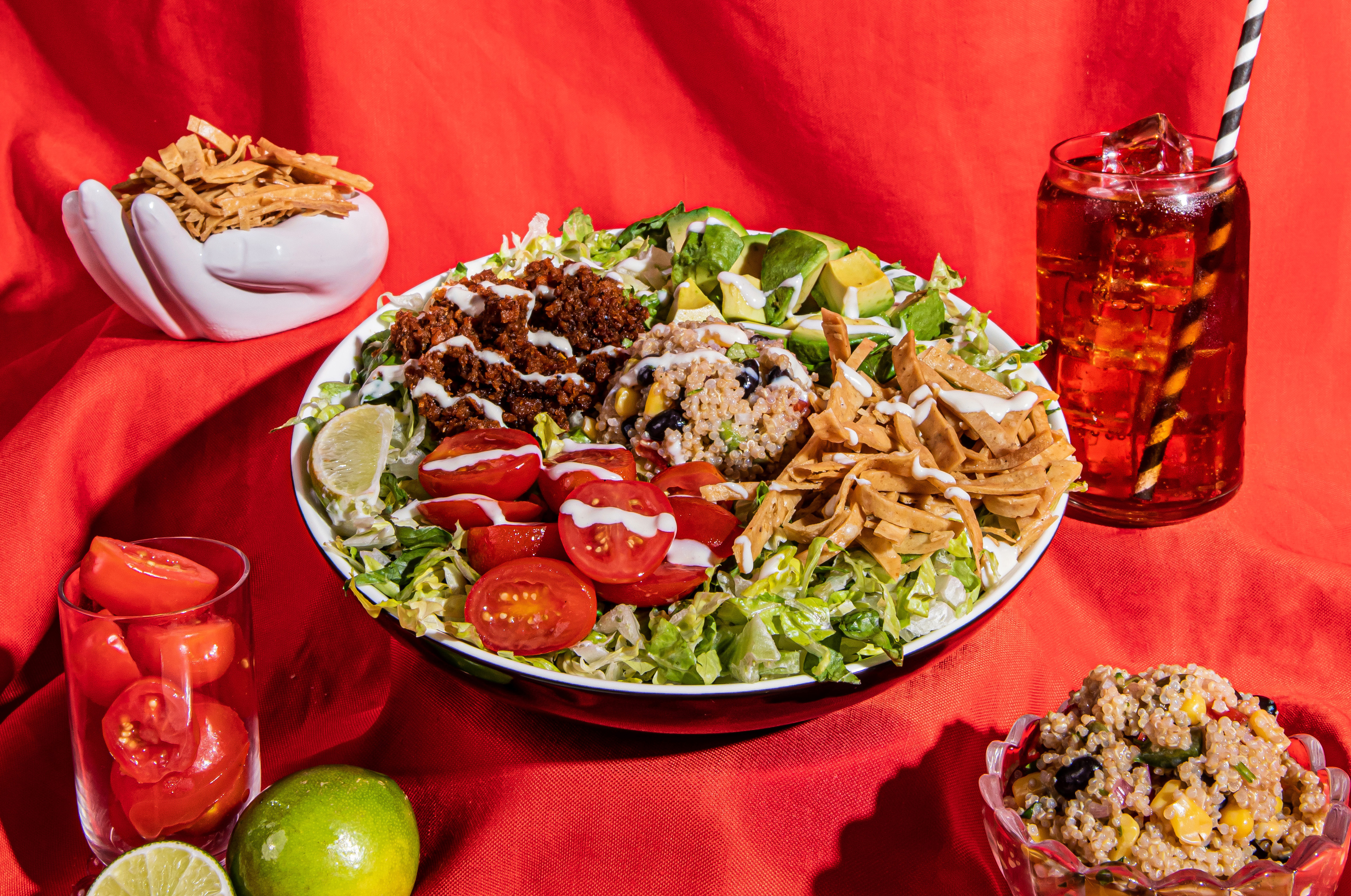A large bowl filled with lettuce, tomatoes, quinoa, and strips of tortilla chip with limes, tomatoes, and a drink arranged around it on a red background