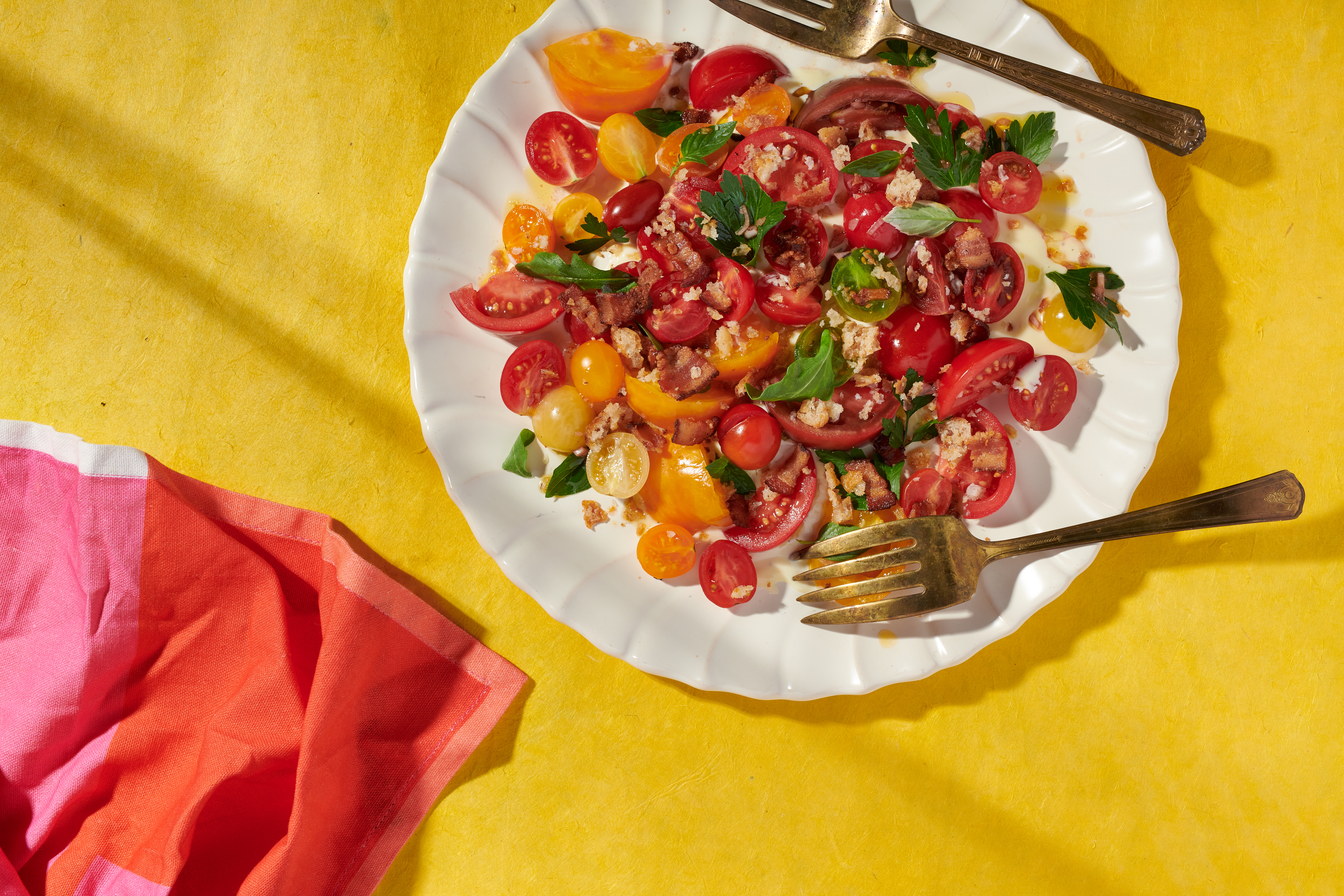 A BLT salad and two gold forks sit on a white plate. The plate is set on a bright-yellow table, with a hot-pink napkin unfolded next to it.