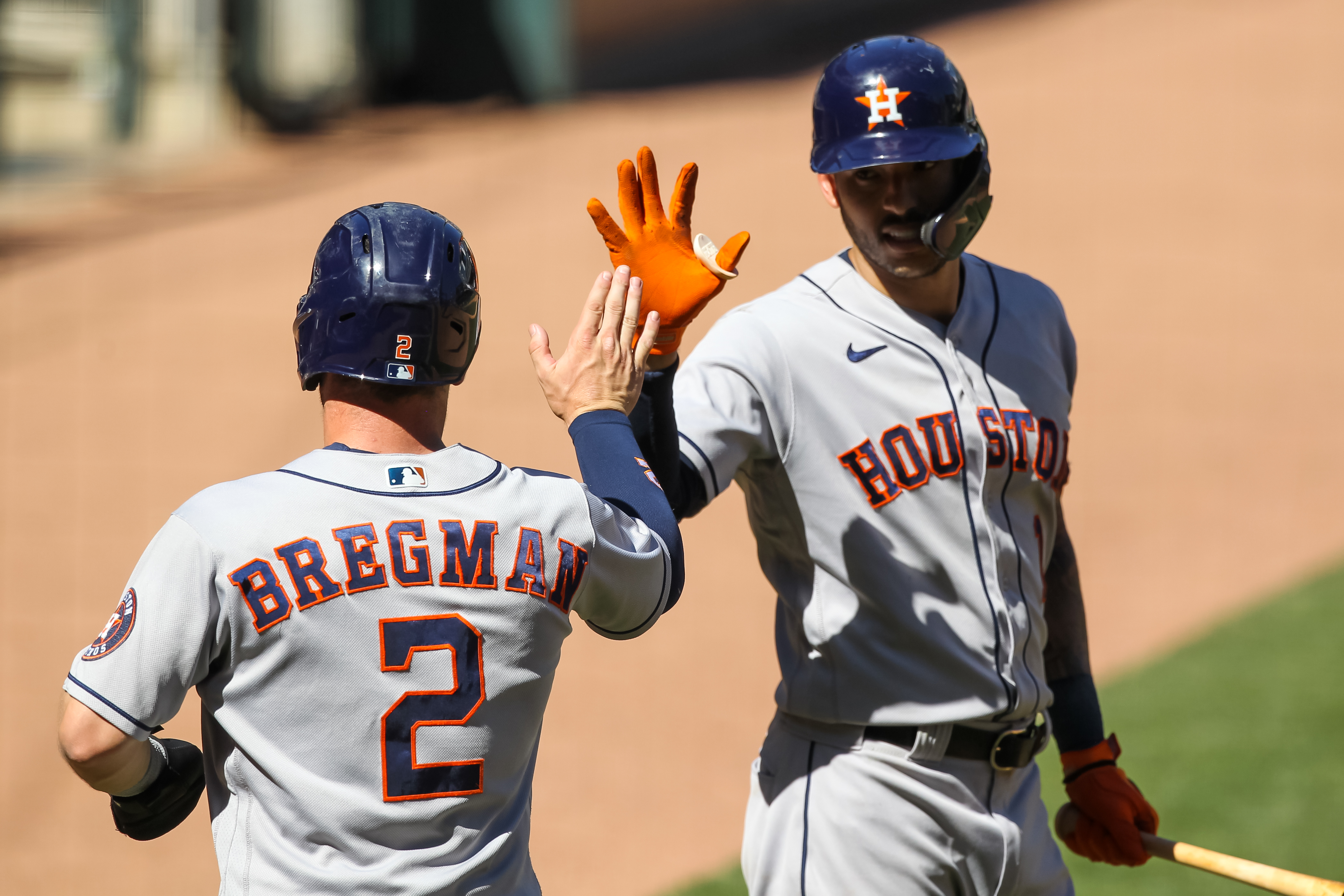 Carlos Correa celebrates with Alex Bregman after Bregman scored a run off a sacrifice fly by Robel Garcia of the Houston Astros in the ninth inning of the game against the Minnesota Twins at Target Field on June 13, 2021 in Minneapolis, Minnesota. The Astros defeated the Twins 14-3.