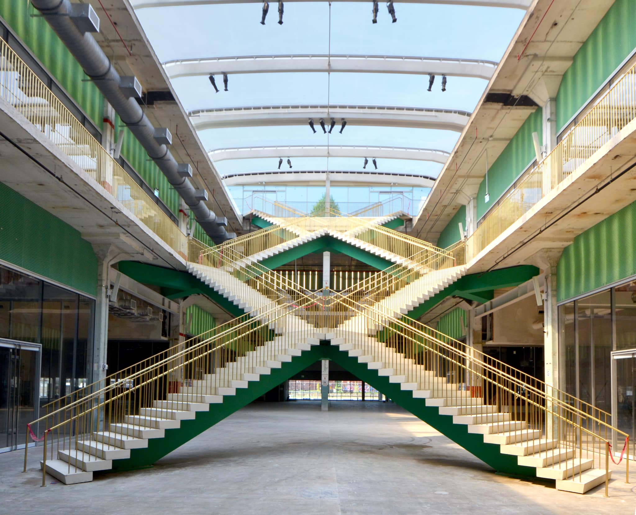 the interior of a building with in interesting, X-shaped stairwell