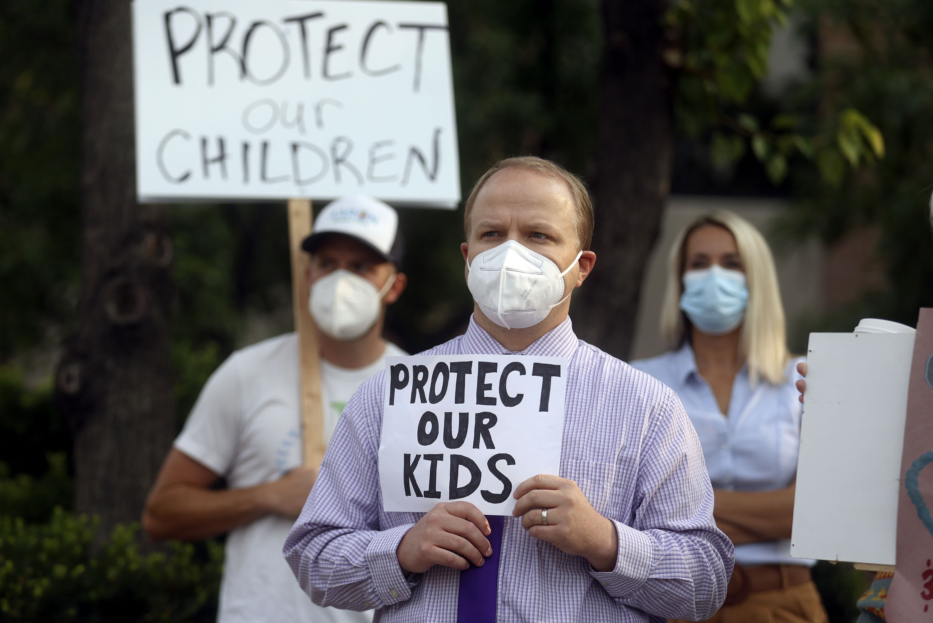 A man holds a sign supporting school mask mandates.