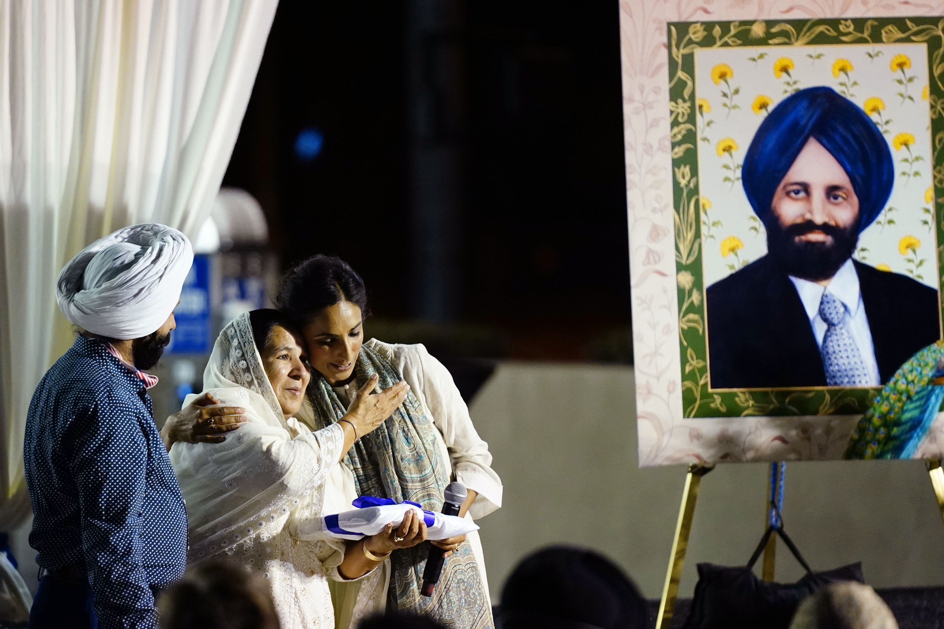 Valarie Kaur, right, of the Revolutionary Love Project, hugs Harjinder Kaur Sodhi, the widow of Balbir Singh Sodhi, middle, as Balbir's brother Rana Singh Sodhi, left, looks on at a memorial service on the 20th anniversary of the murder of Balbir Singh Sodhi Wednesday, Sept. 15, 2021, in Mesa, Ariz.