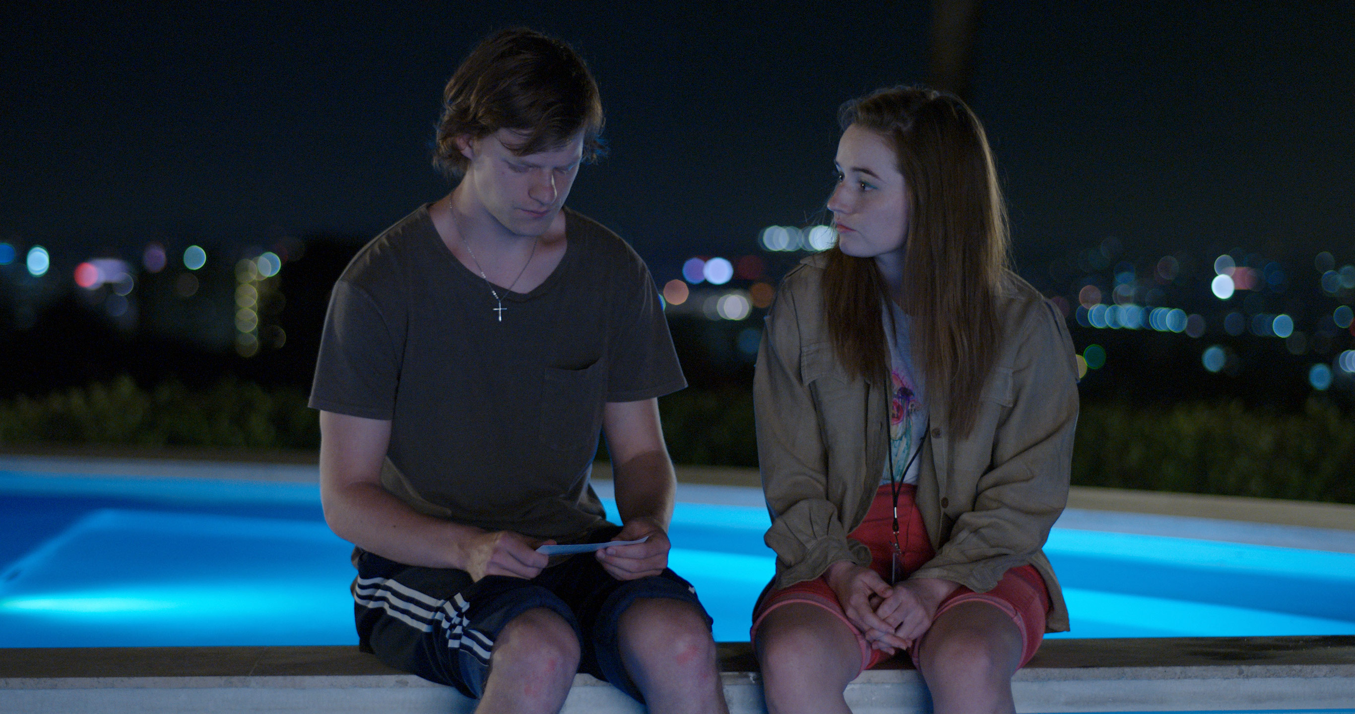 Lucas Hedges and Kaitlyn Dever sit on the edge of the pool in the third episode of FX on Hulu's The Premise