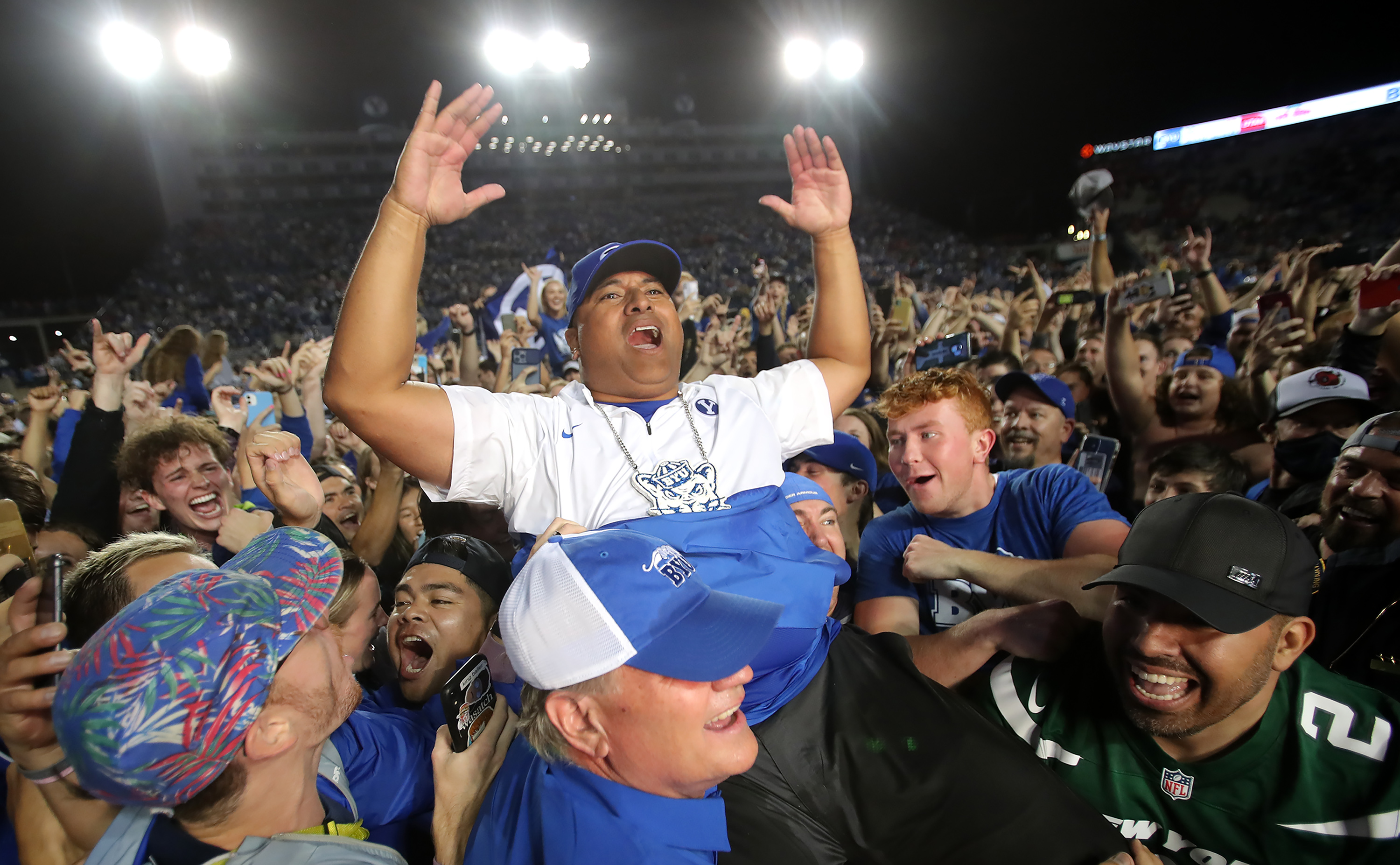 Brigham Young Cougars head coach Kalani Sitake celebrates the win as he is lifted into the air by fans as BYU defeats Utah.