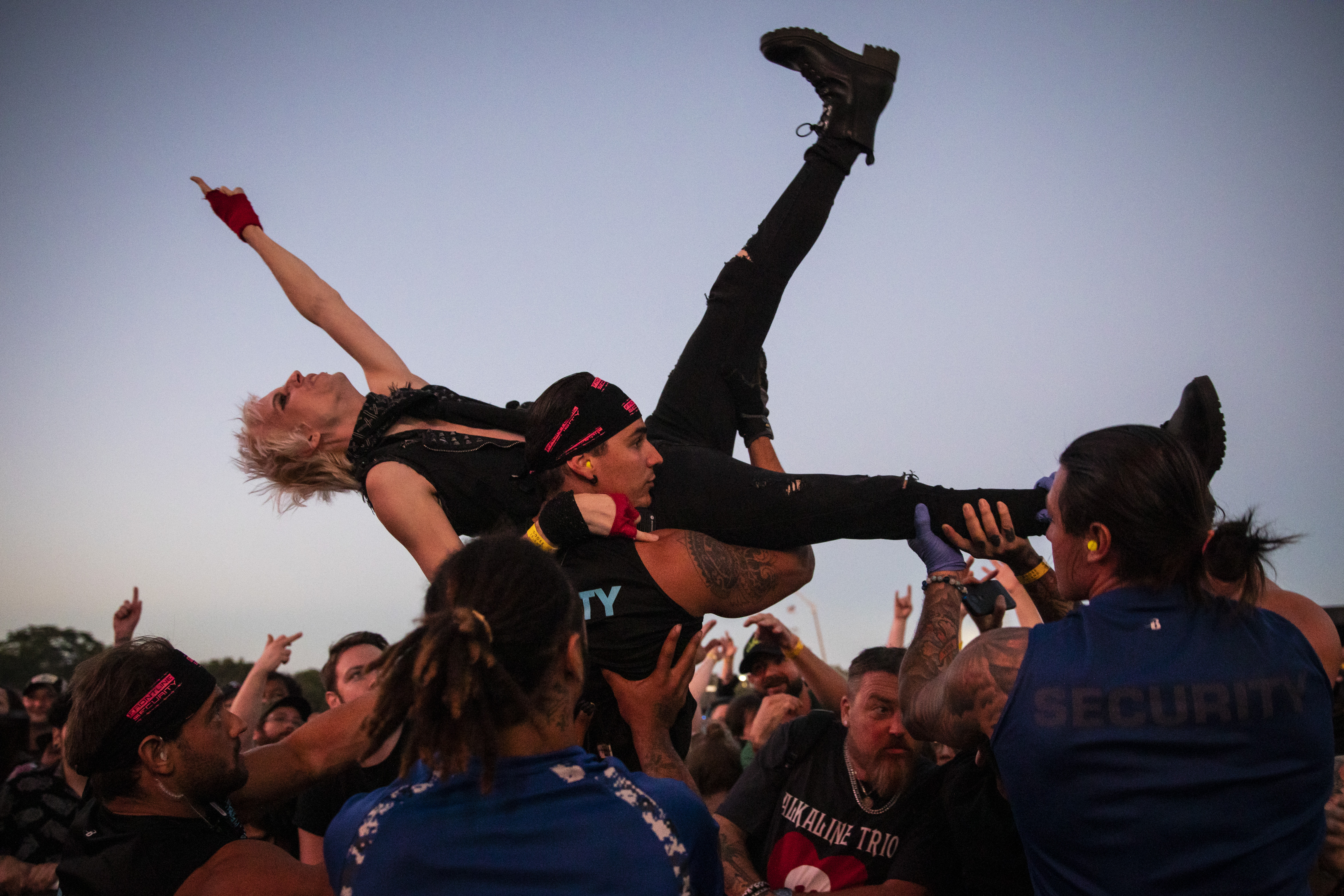 Security lifts a crowd-surfing fan during Alkaline Trio's performance Thursday at Riot Fest.