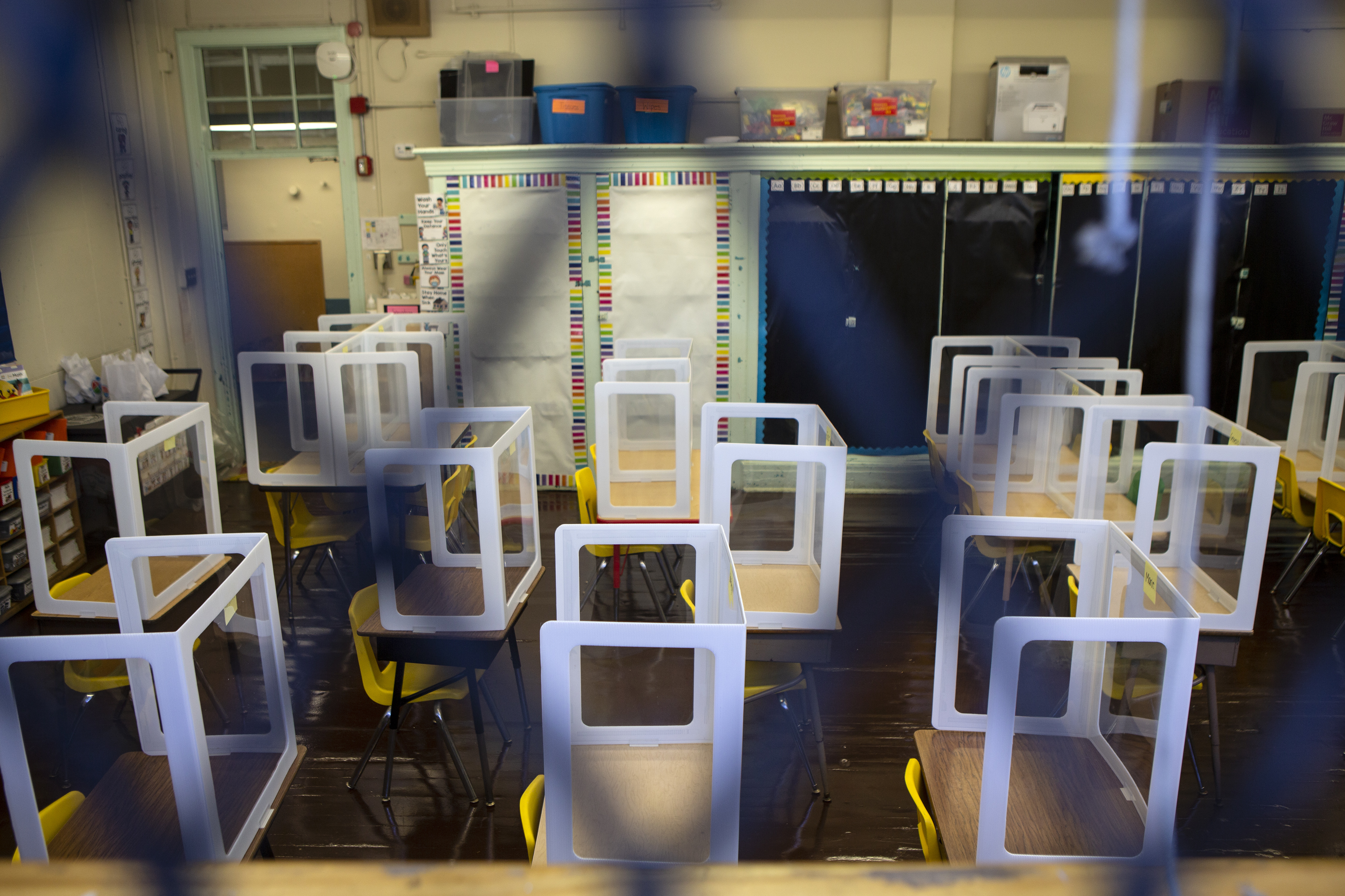 An empty classroom is seen behind a small gate, with plastic barriers on every desk due to COVID concerns.