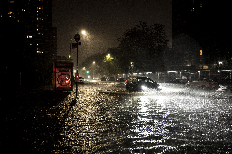 A sedan tries to drive through rising flood water down Leonard St in Brooklyn.