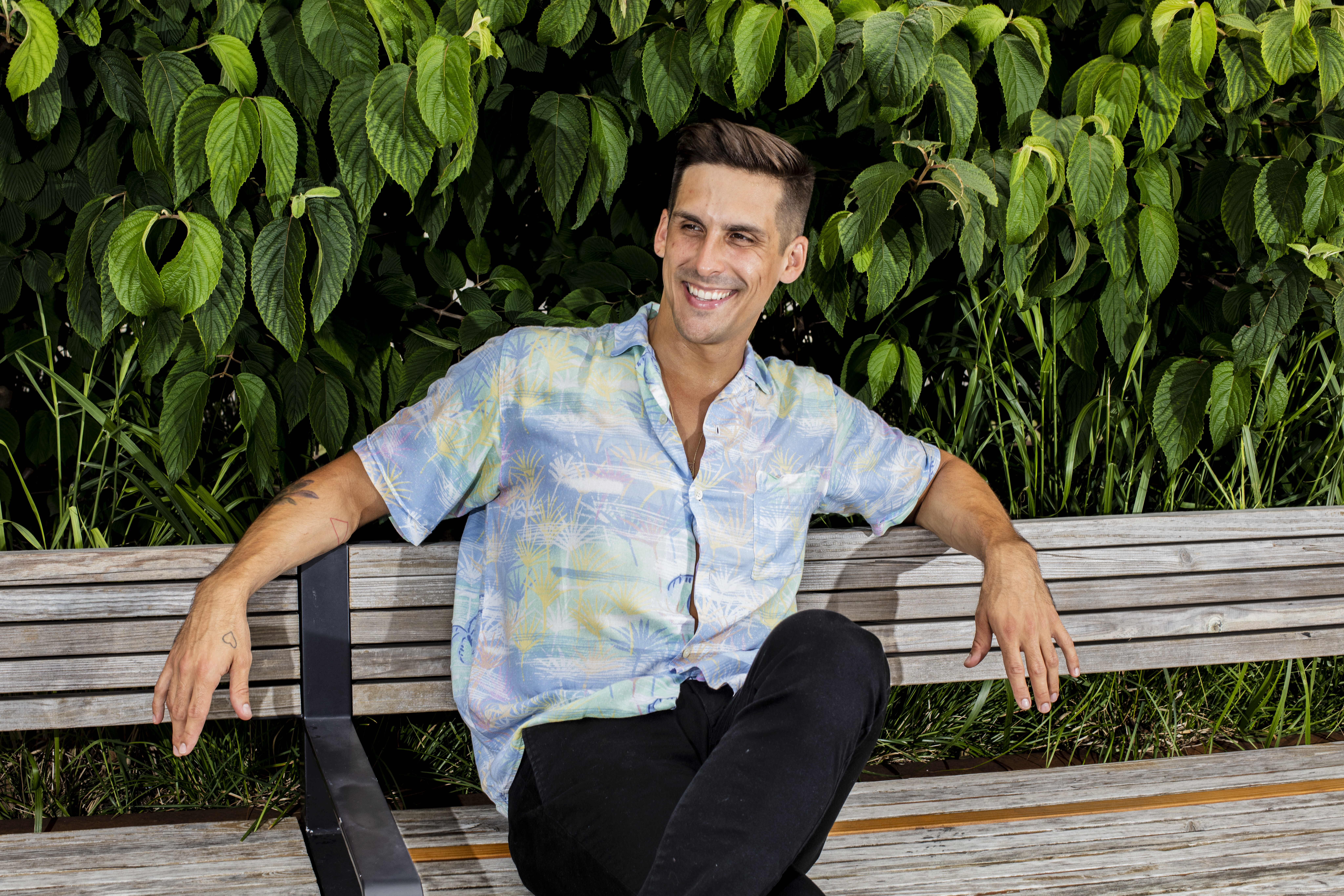 Cody Rigsby sits smiling on a park bench with shrubbery behind him.