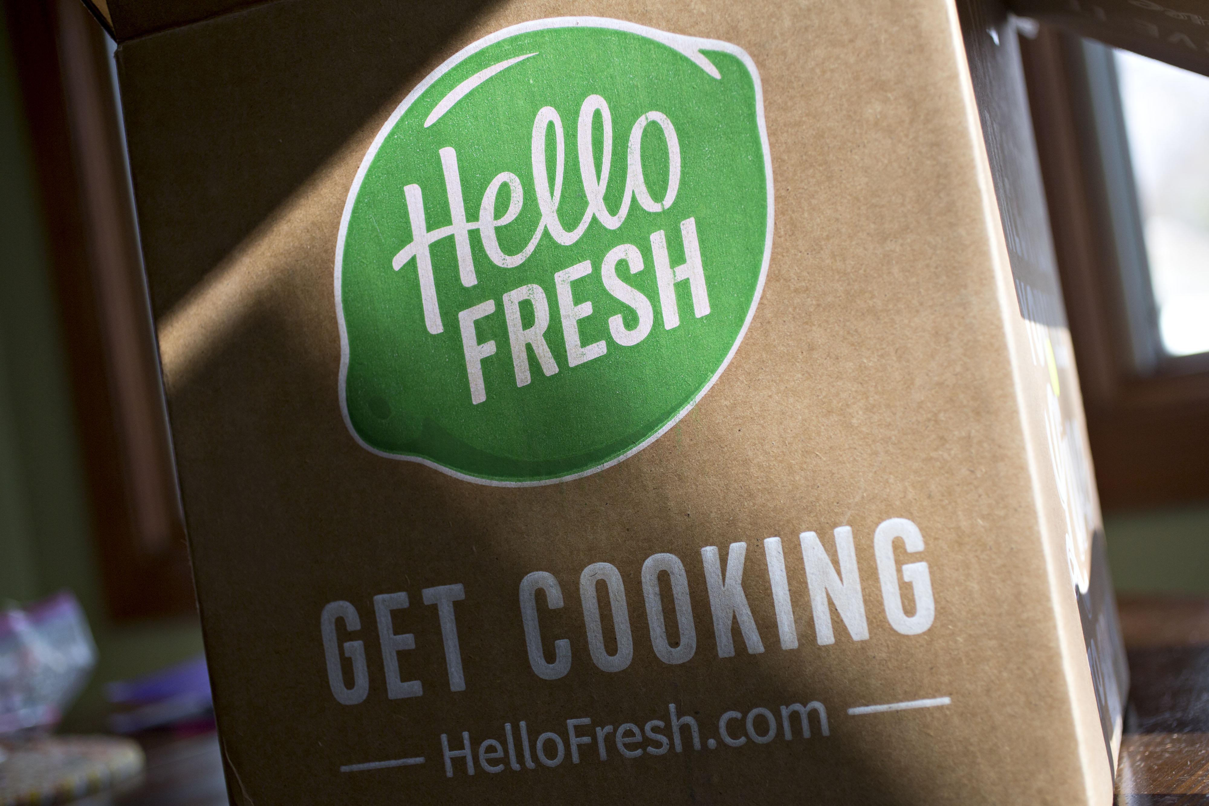 Cardboard box with green HelloFresh logo on it in dappled light