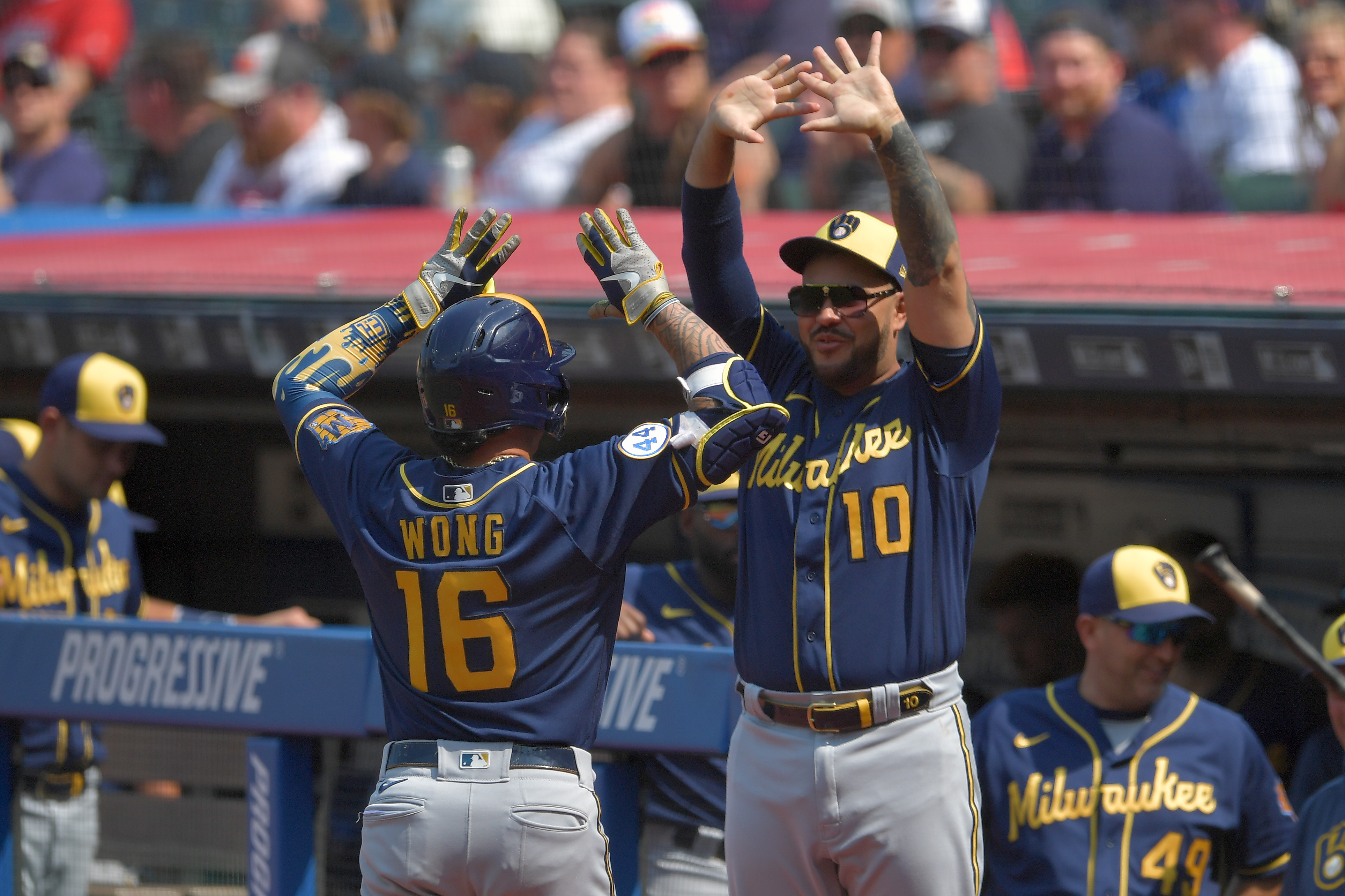 Kolten Wong #16 celebrates with Omar Narvaez #10 of the Milwaukee Brewers after Wong hit a solo homer during the first inning against the Cleveland Indians at Progressive Field on September 12, 2021 in Cleveland, Ohio.