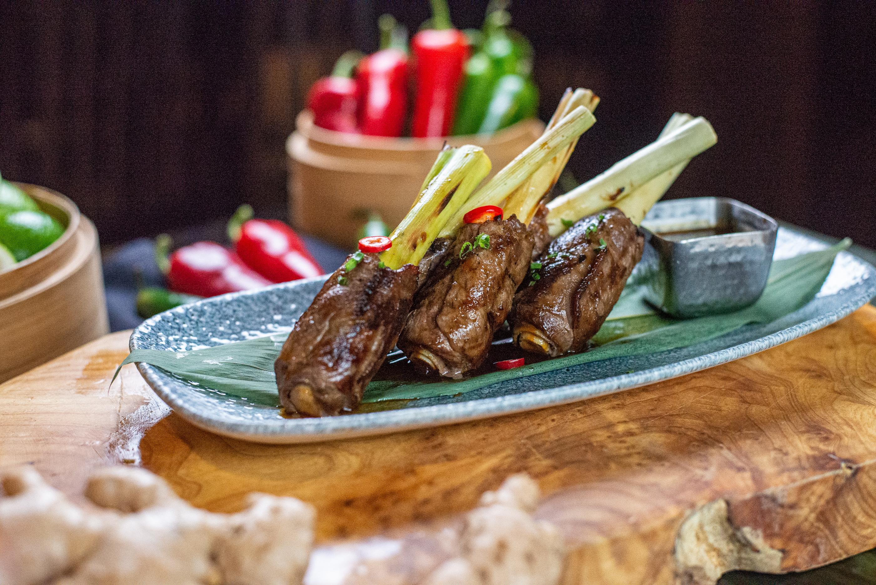 A plate holds three lemongrass beef lollipops
