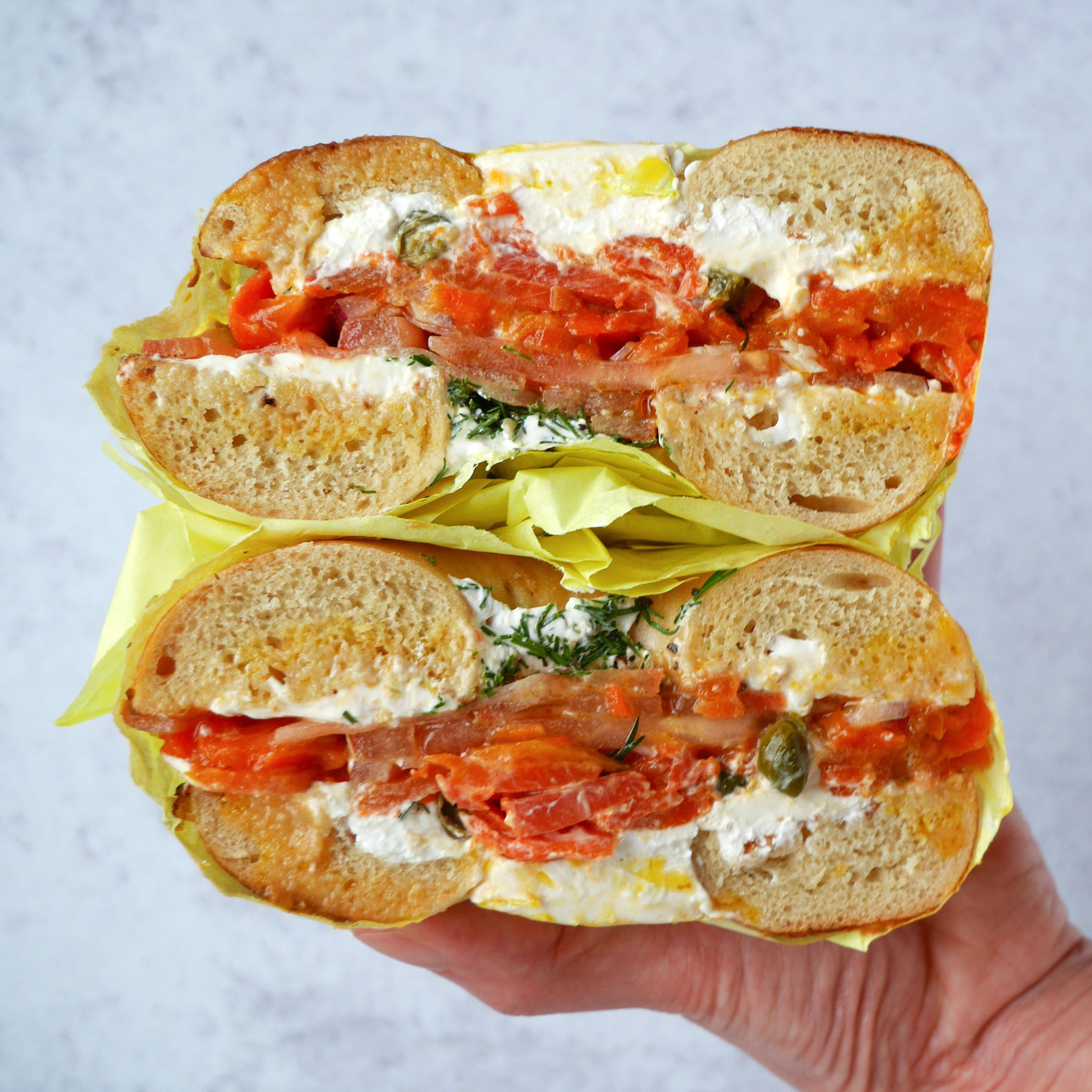 A hand holds a bagel filled with slices of orange carrot, with schmear and herbs on either side. This bagel was sold at the original Ben & Esther's location in Portland, Oregon