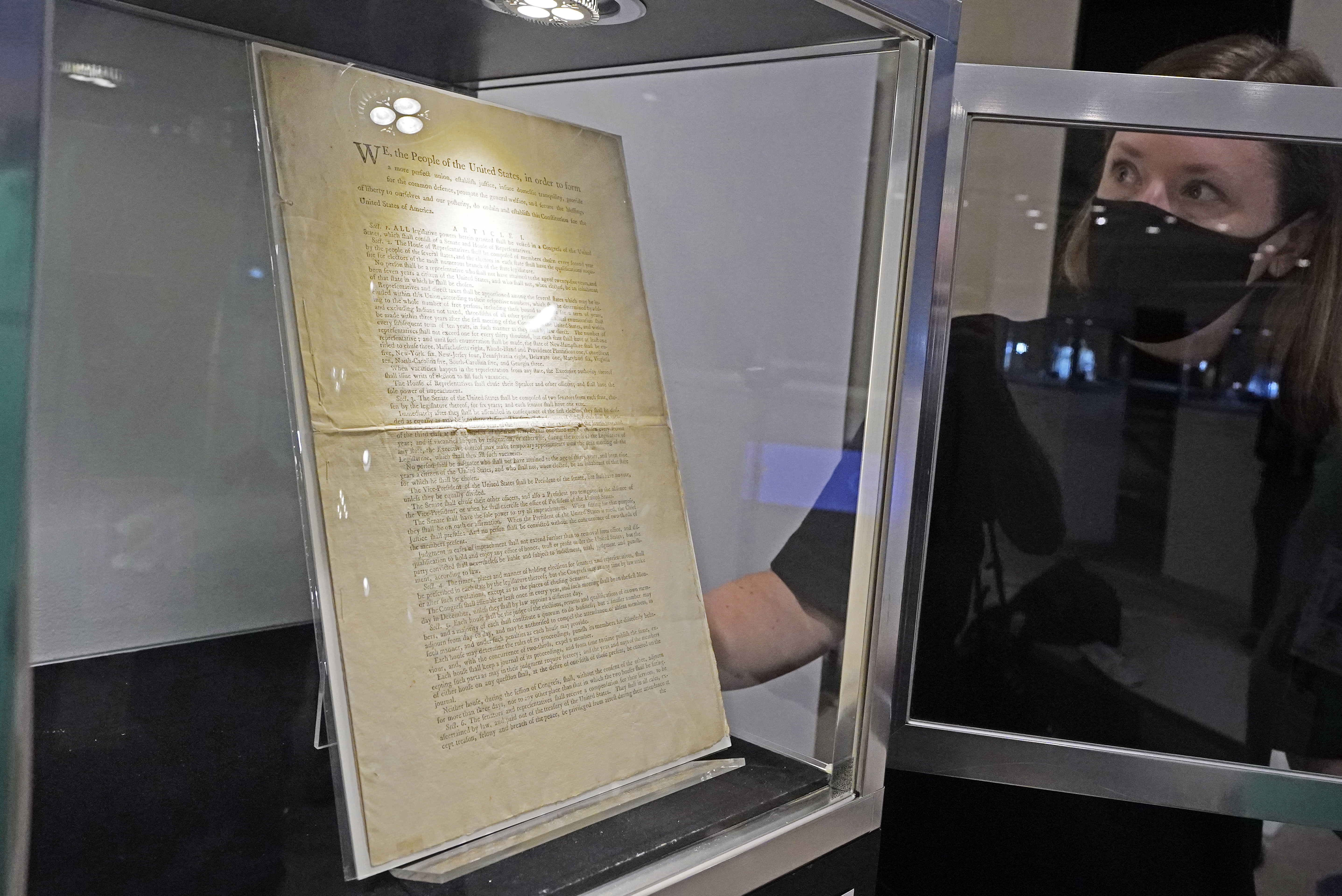 Ella Hall, a specialist in Books and Manuscripts at Sotheby's in New York, places a 1787 printed copy of the U.S. Constitution in its display case on Friday, Sept. 17, 2021.