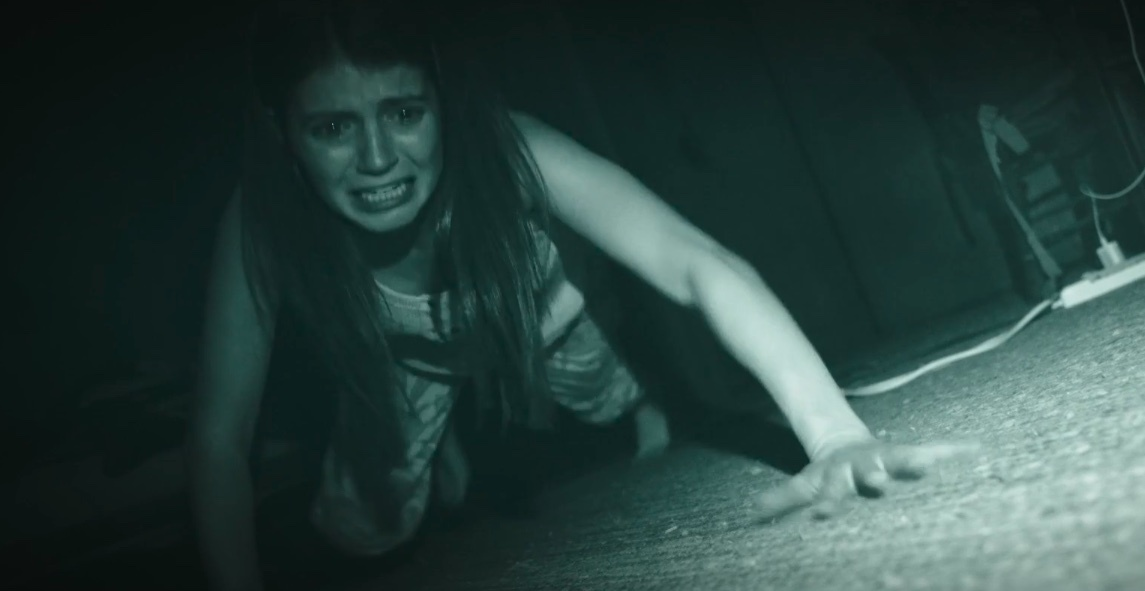 A character crawls around in the dark in Paranormal Activity: Next of Kin