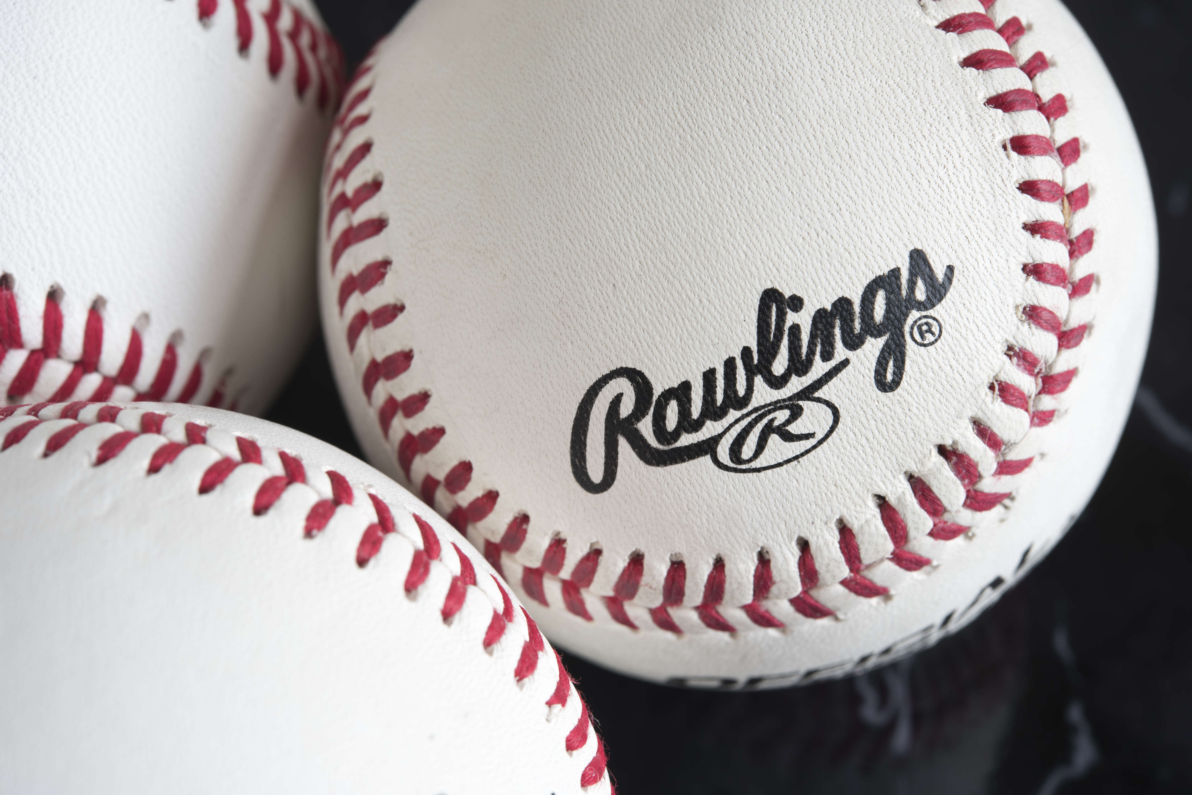 Rawlings baseballs with white surface and red stitches,...