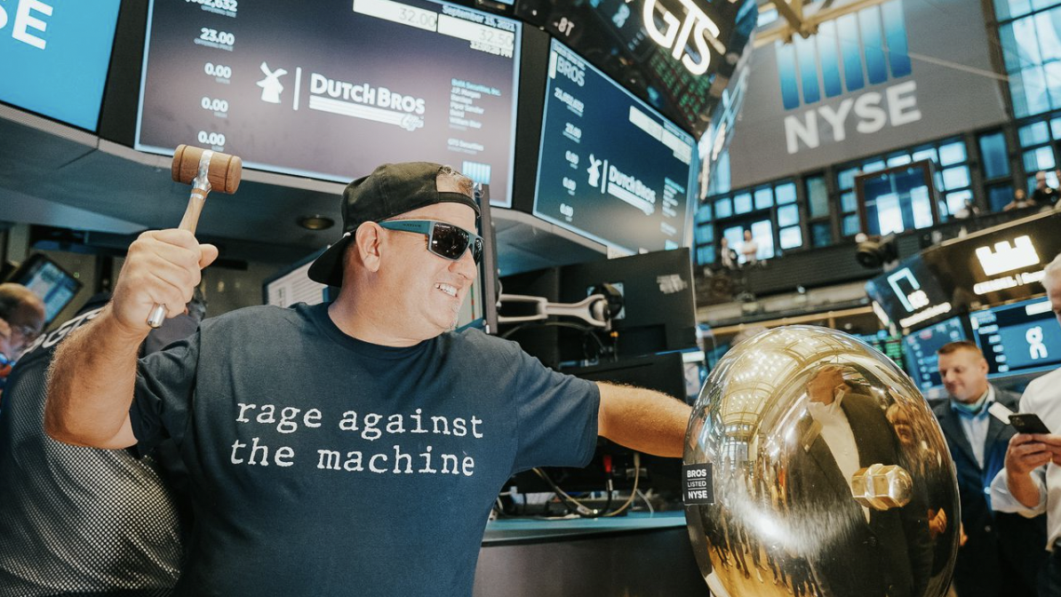 A man in a backwards baseball cap rings the trade bell on the floor of the New York Stock Exchange.