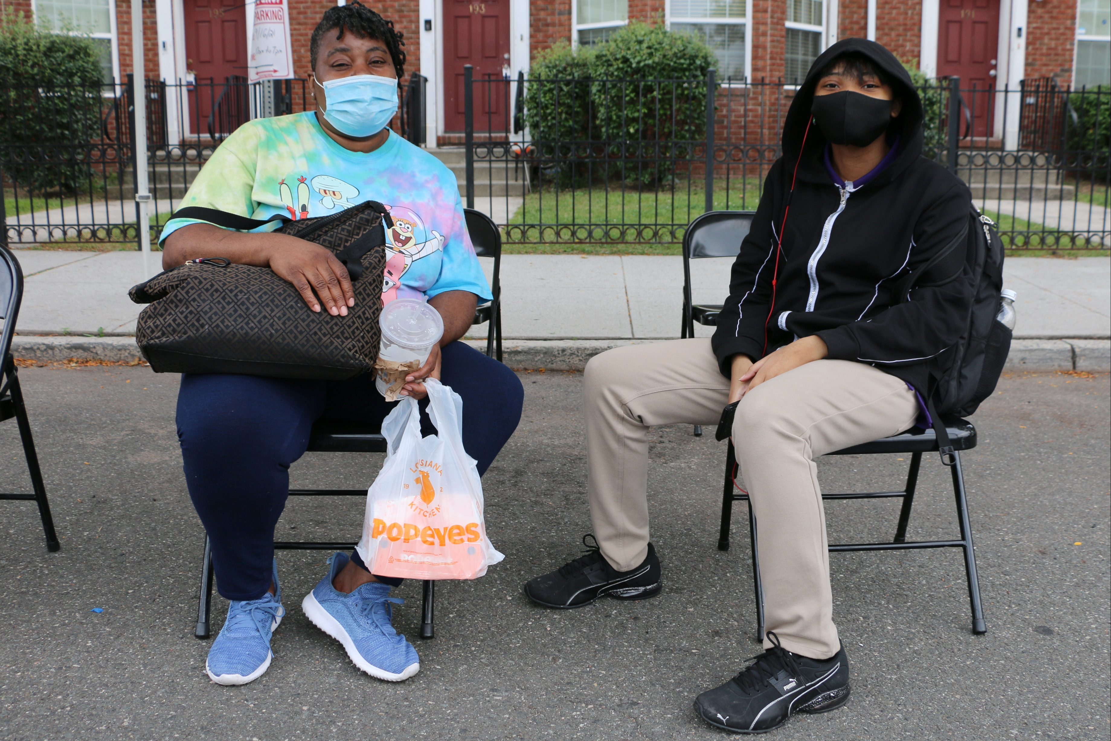 A mother and daughter, wearing masks, sit on folding chairs outside a pop-up COVID vaccination clinic in Newark.