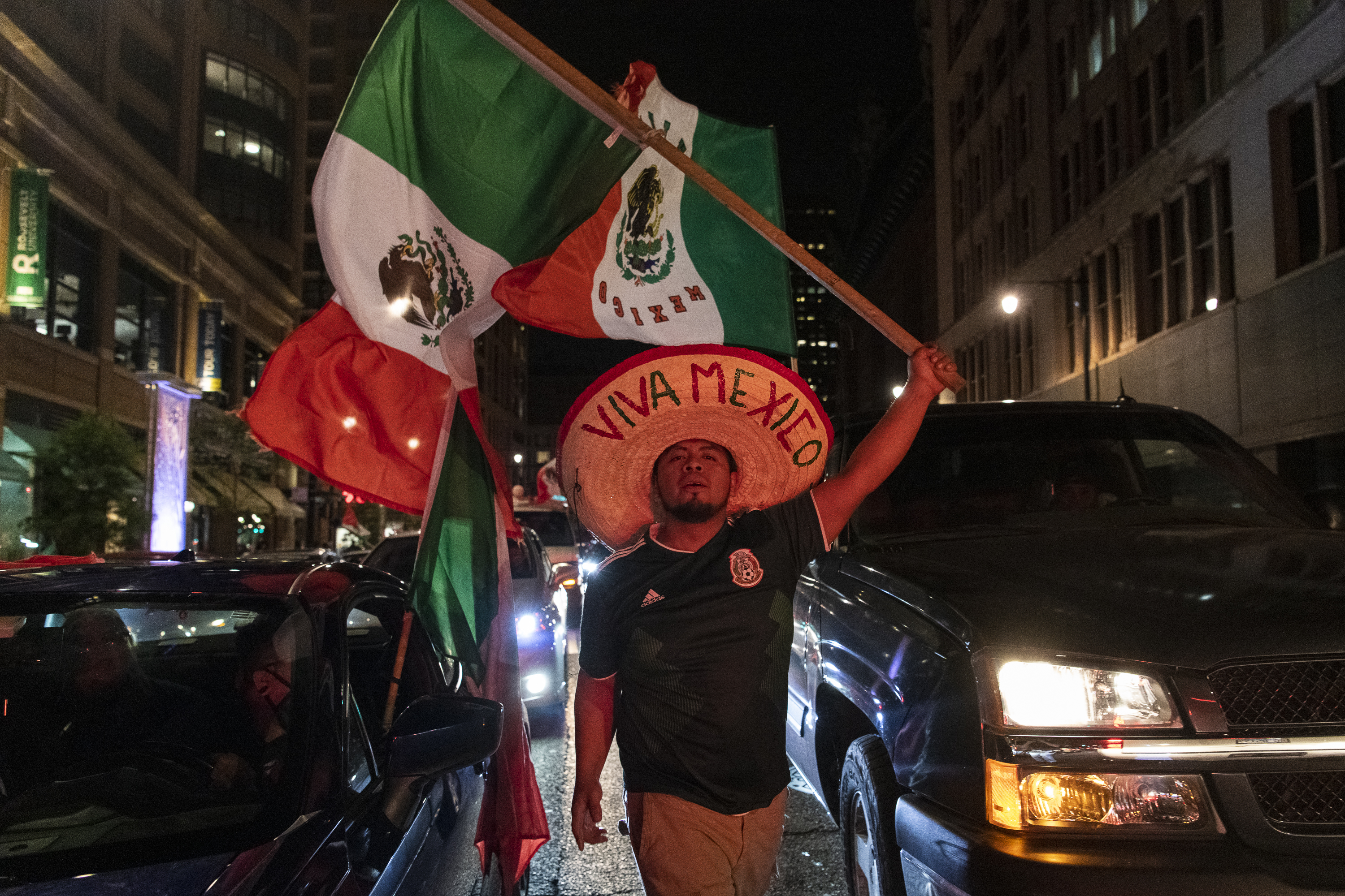 A man walks between vehicles with a Mexican flag on Ida B. Wells Dr. as hundreds of people celebrate in downtown Chicago for Mexican Independence Day last year.