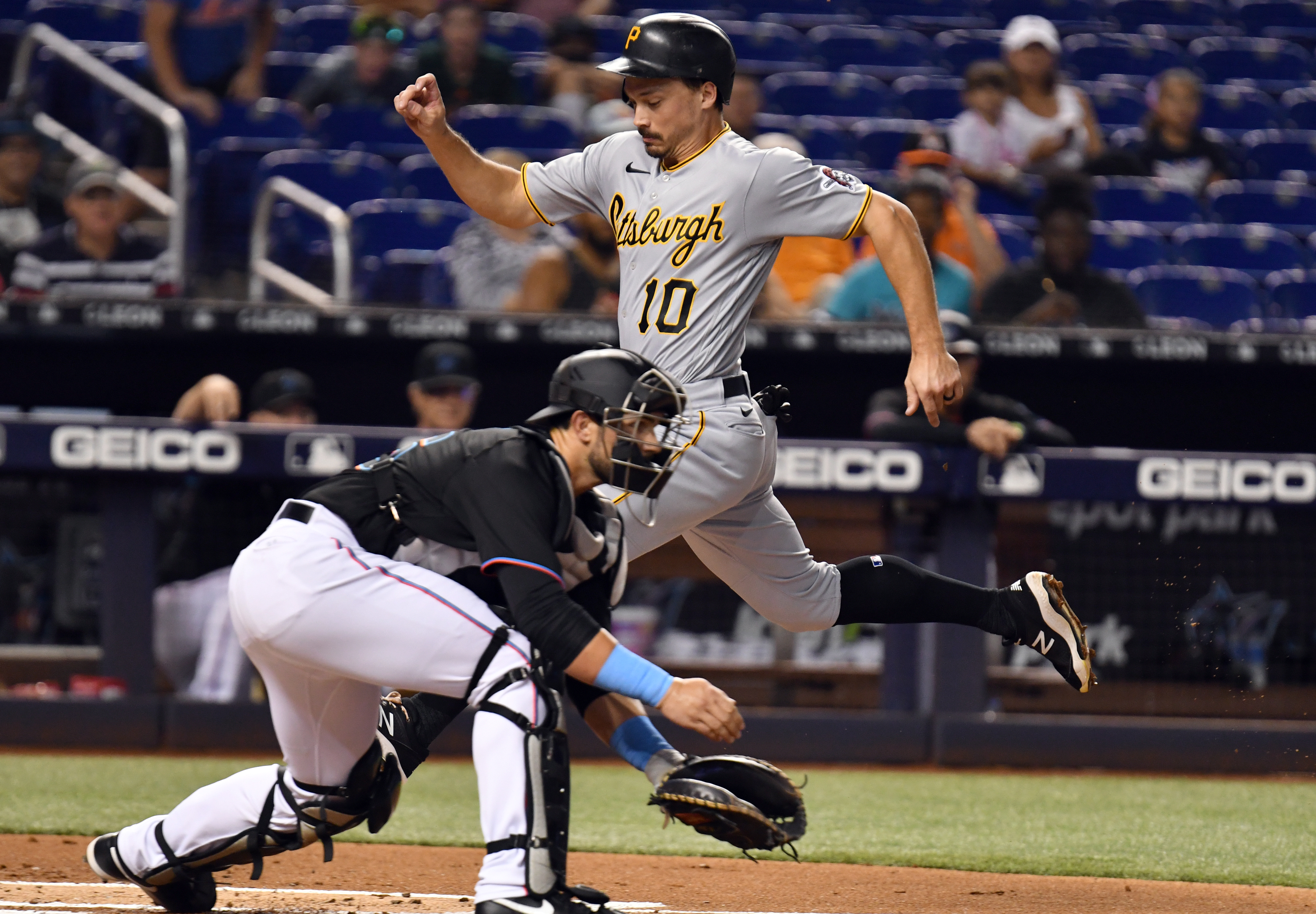 Pittsburgh Pirates left fielder Bryan Reynolds (10) scores a run as Miami Marlins catcher Peyton Henry (86) awaits the throw during the first inning at loanDepot Park