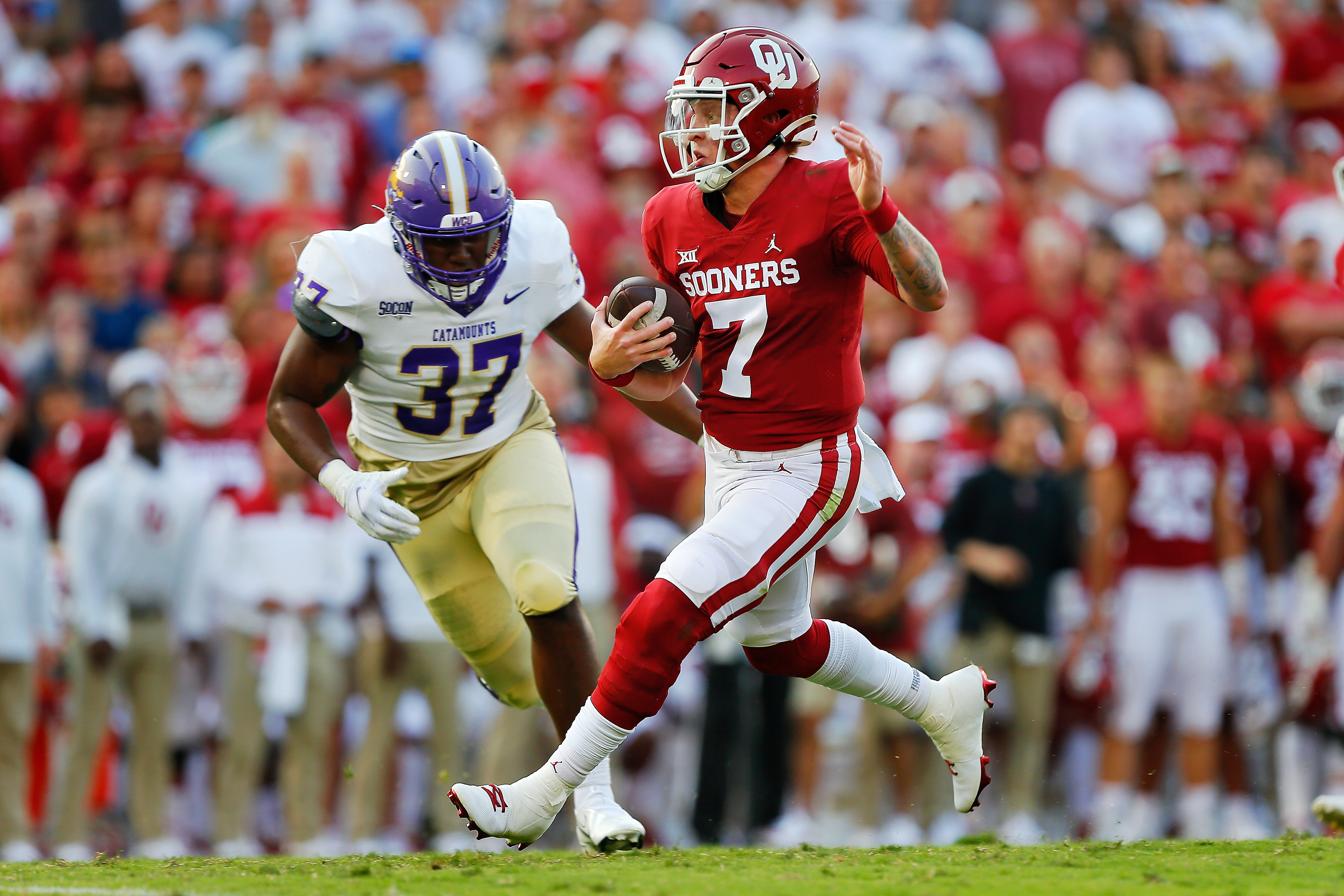 Quarterback Spencer Rattler of the Oklahoma Sooners runs to the one-yard line on a 22-yard run against linebacker Ty Harris of the Western Carolina Catamounts on the last play of the first quarter at Gaylord Family Oklahoma Memorial Stadium on September 11, 2021 in Norman, Oklahoma.