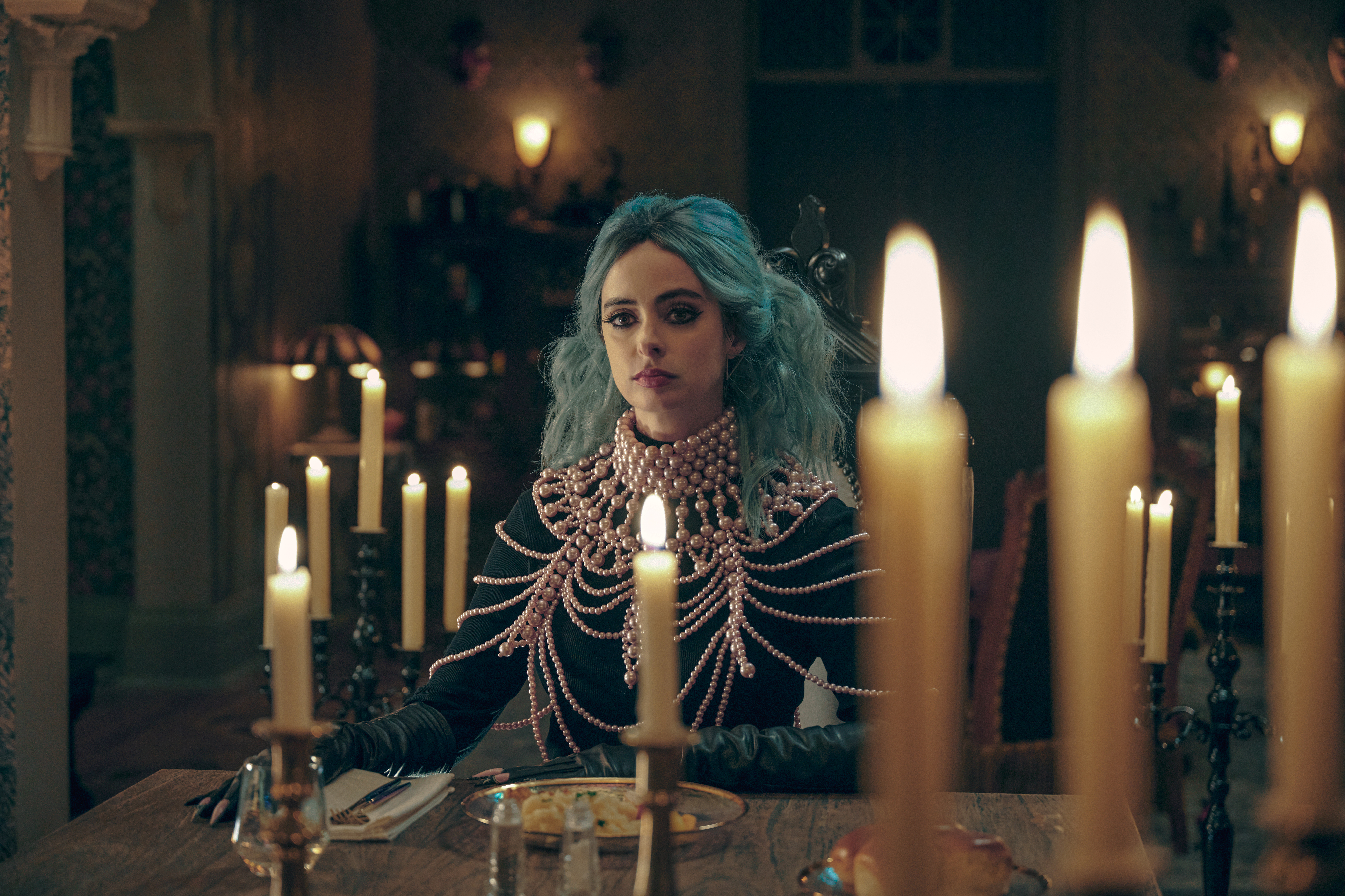 KRYSTEN RITTER as NATACHA in NIGHTBOOKS sitting behind some candles with her bright blue hair