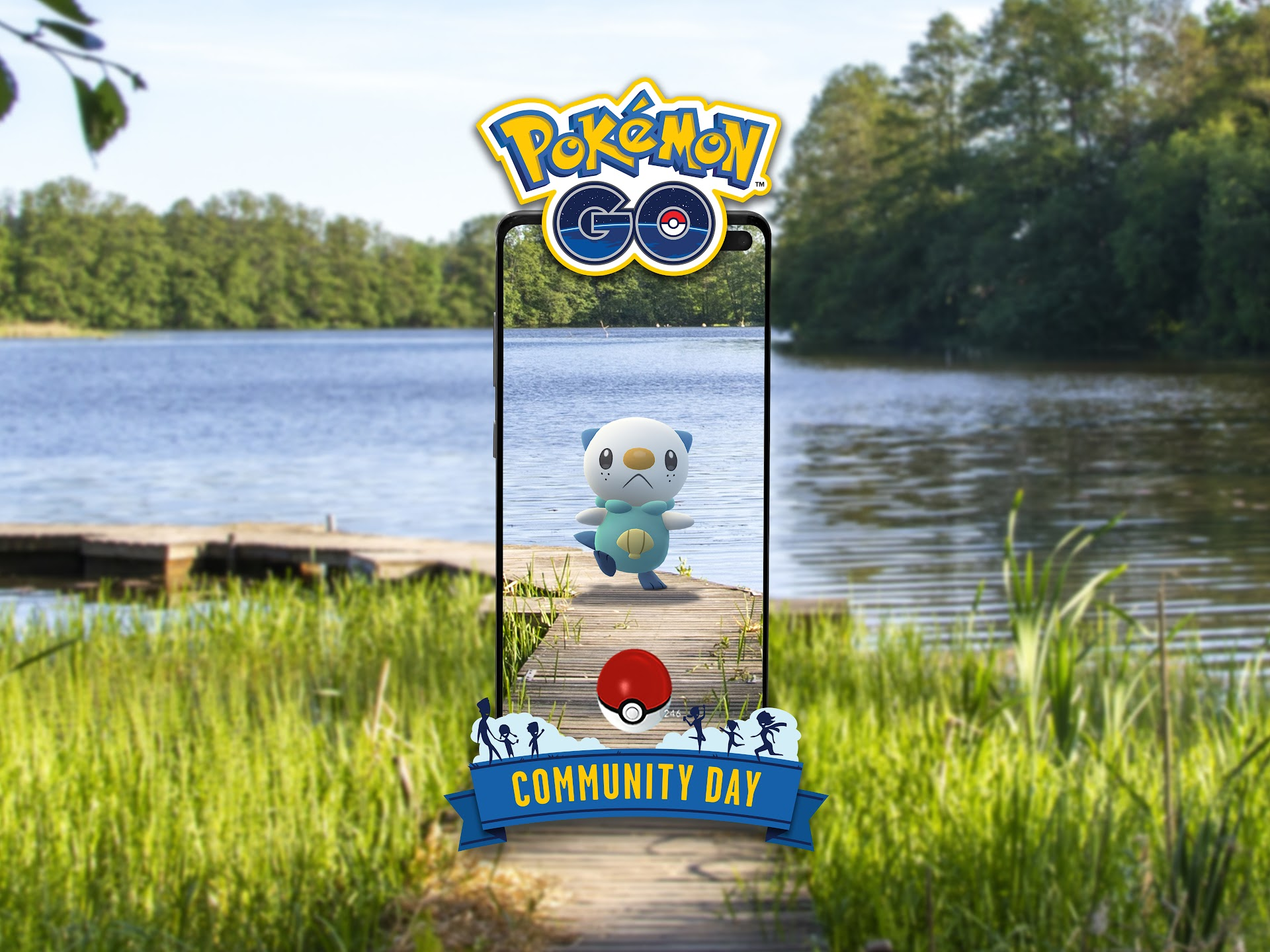 Oshawott, a little otter Pokémon, stands framed by a smart phone in front of a river or lake