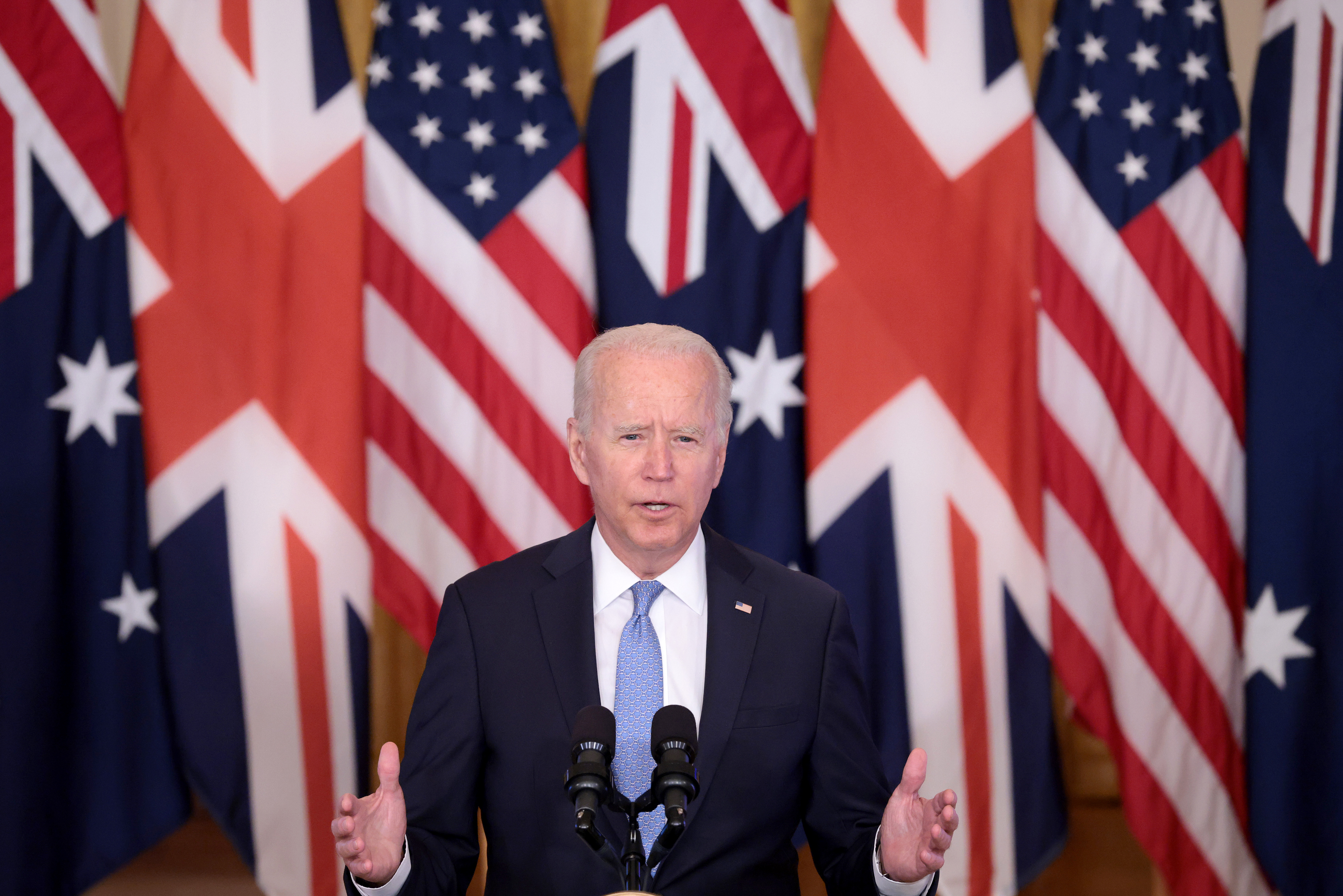 President Joe Biden speaks from the podium in the East Room of the White House in front of a row of US, British, and Australian flags.