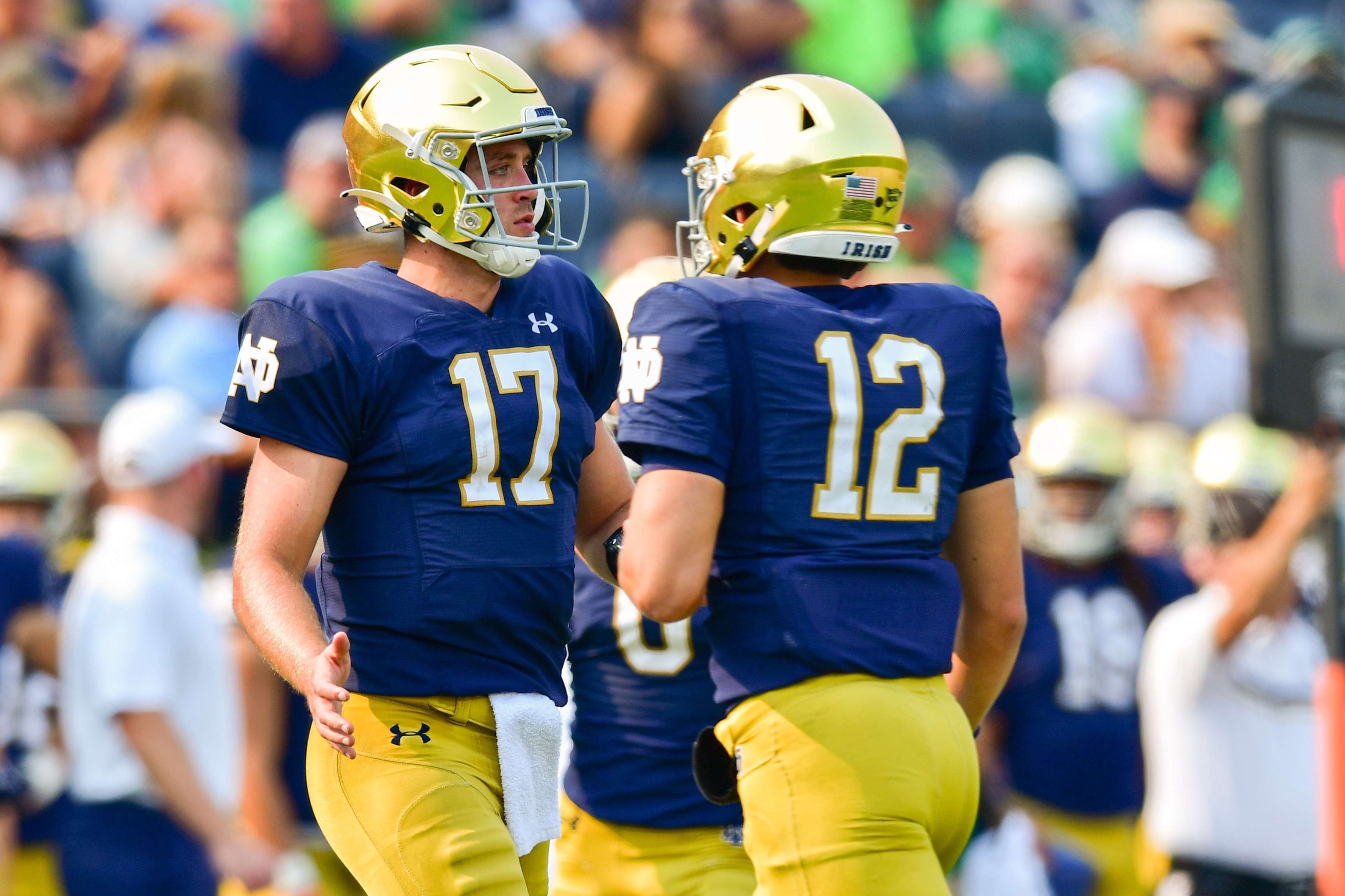 Notre Dame Fighting Irish quarterback Jack Coan runs on to the field as quarterback Tyler Buchner leaves the field in the third quarter at Notre Dame Stadium.