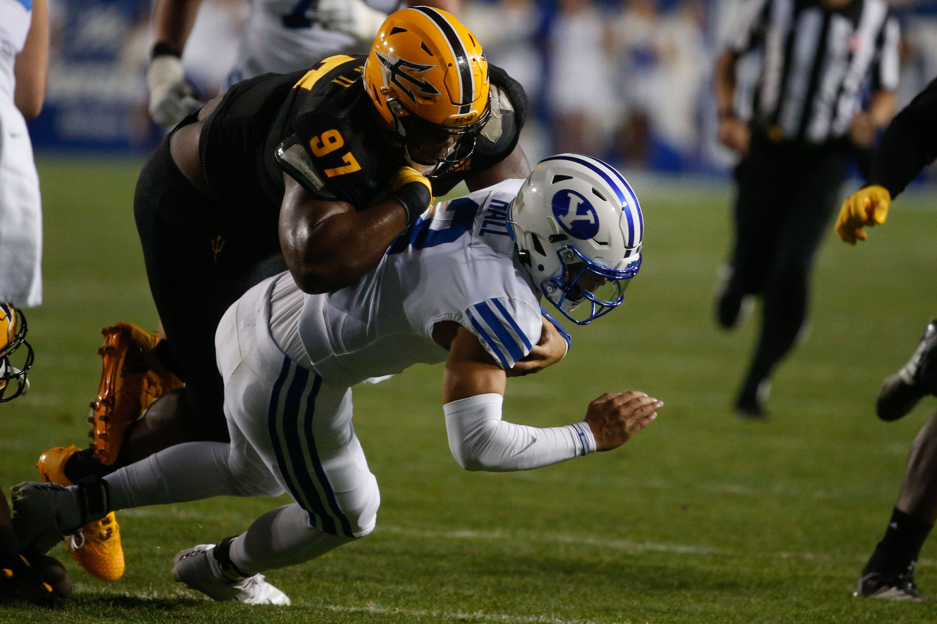 Brigham Young quarterback Jaren Hall, right, gets tackled by Arizona State defensive lineman Shannon Forman.