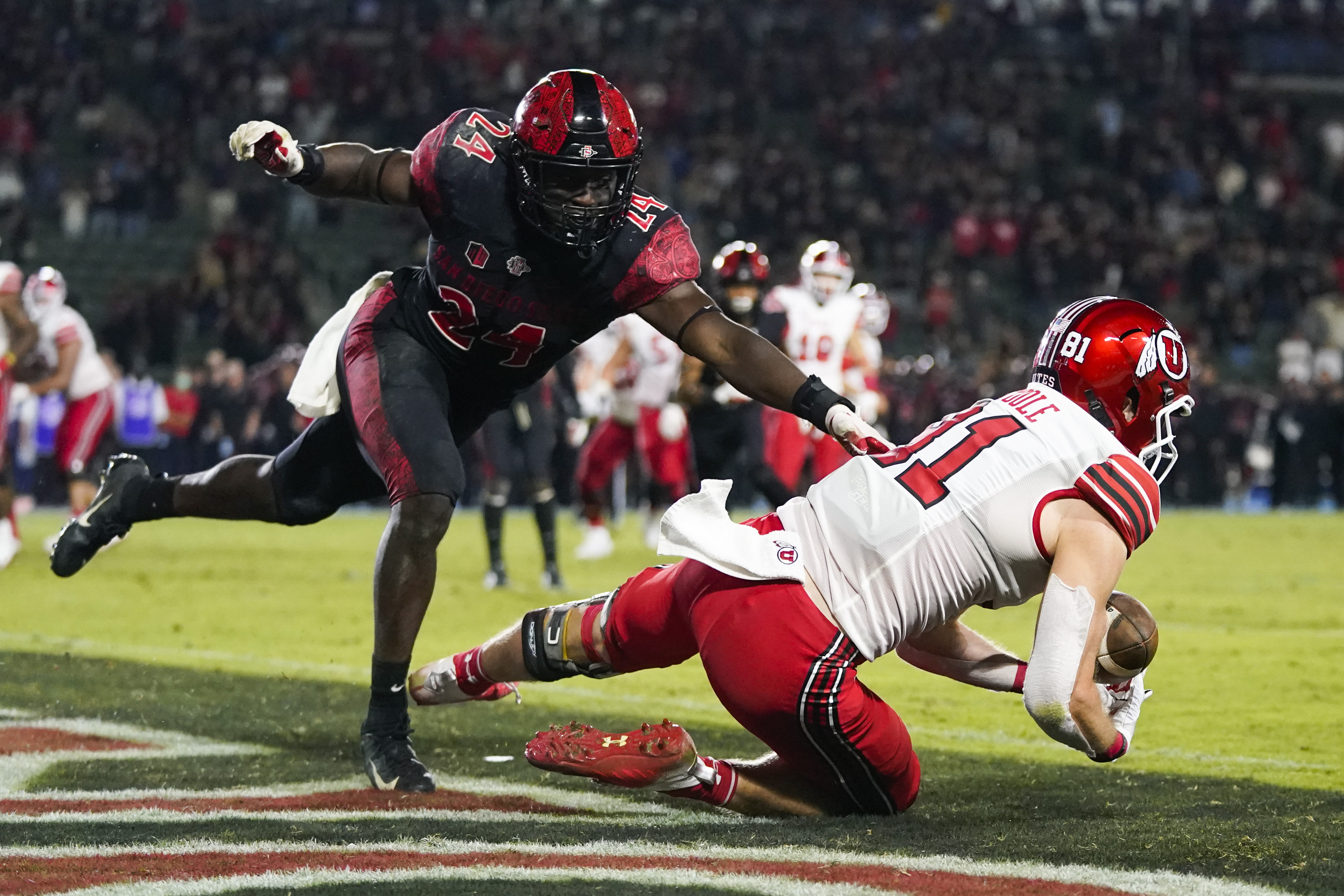 Utah wide receiver Connor O'Toole tries to catch a pass in the end zone ahead of San Diego State linebacker Segun Olubi.