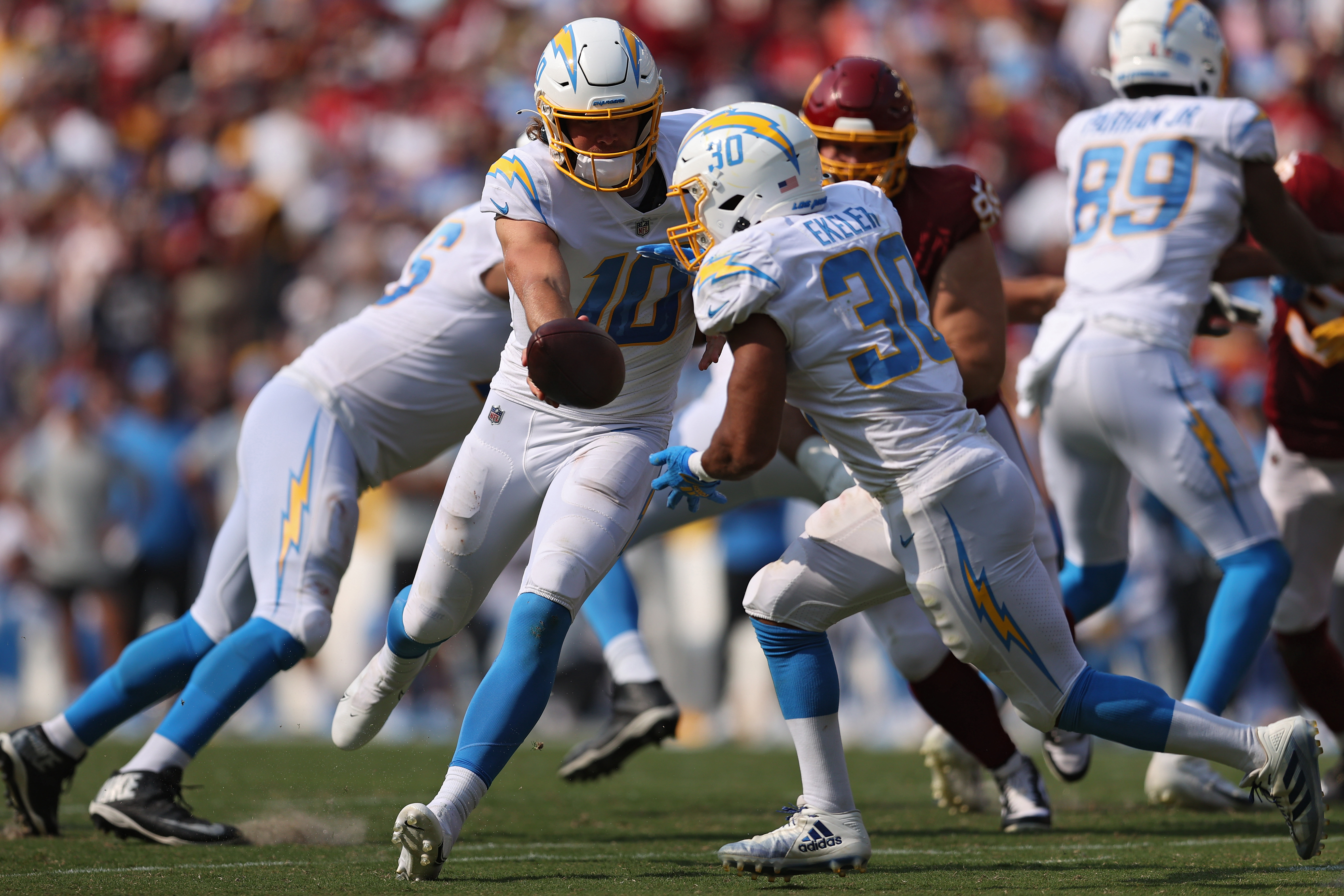 Justin Herbert of the Los Angeles Chargers hands off the ball to Austin Ekeler against the Washington Football Team at FedExField on September 12, 2021 in Landover, Maryland.
