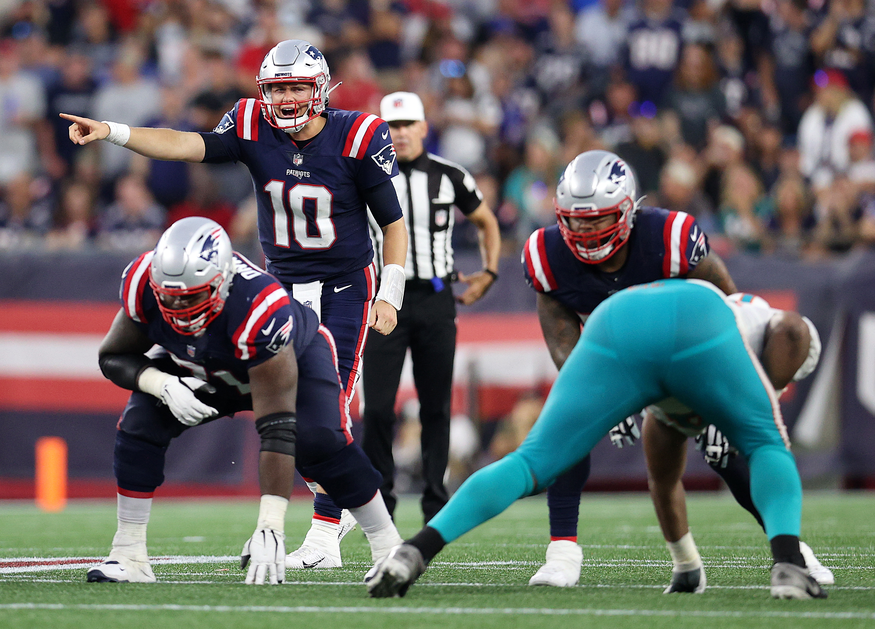 Mac Jones #10 of the New England Patriots directs the offense against the Miami Dolphins at Gillette Stadium on September 12, 2021 in Foxborough, Massachusetts.