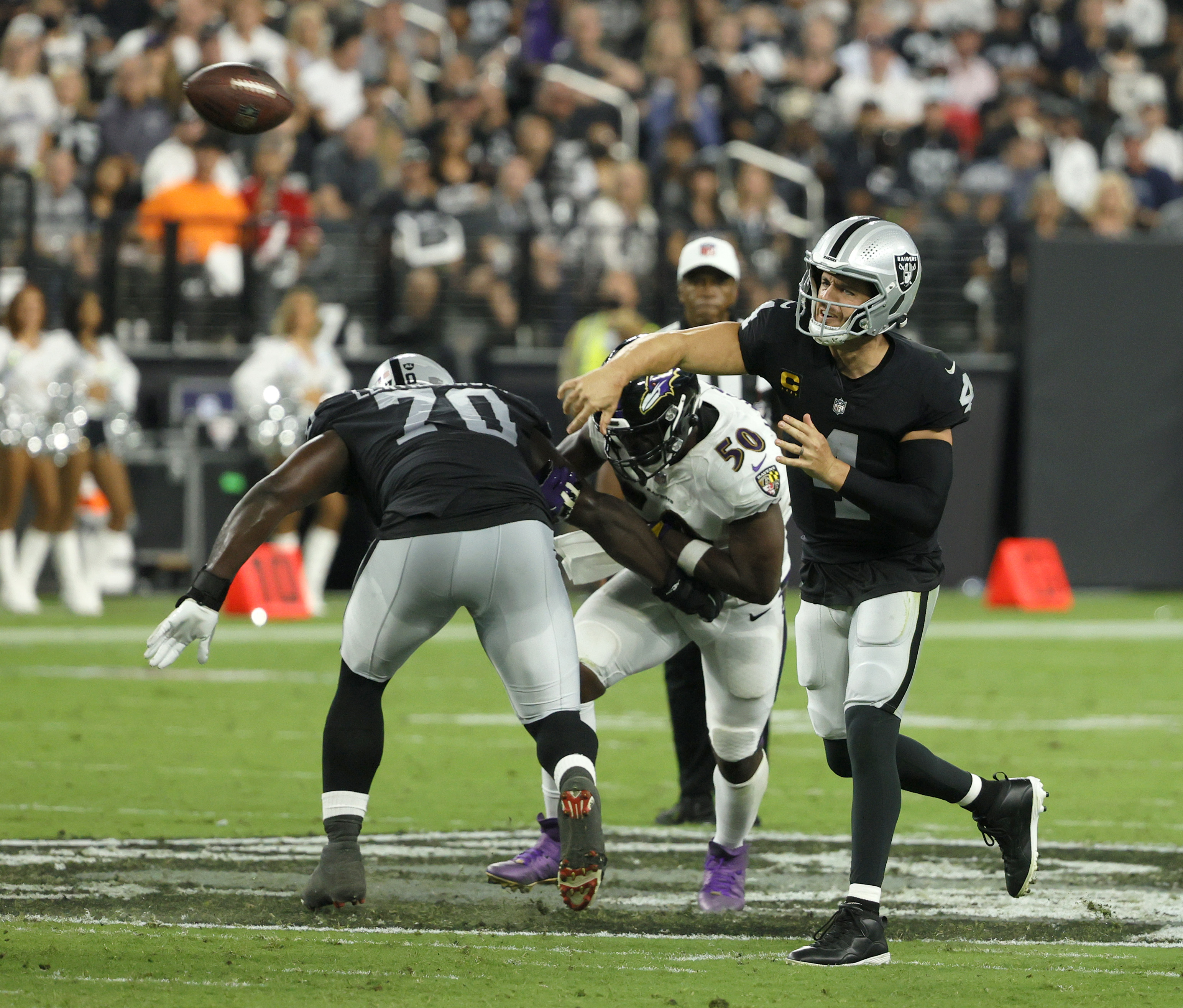 Quarterback Derek Carr #4 of the Las Vegas Raiders throws as offensive tackle Alex Leatherwood #70 of the Raiders blocks linebacker Justin Houston #50 of the Baltimore Ravens during their game at Allegiant Stadium on September 13, 2021 in Las Vegas, Nevada. The Raiders defeated the Ravens 33-27 in overtime.