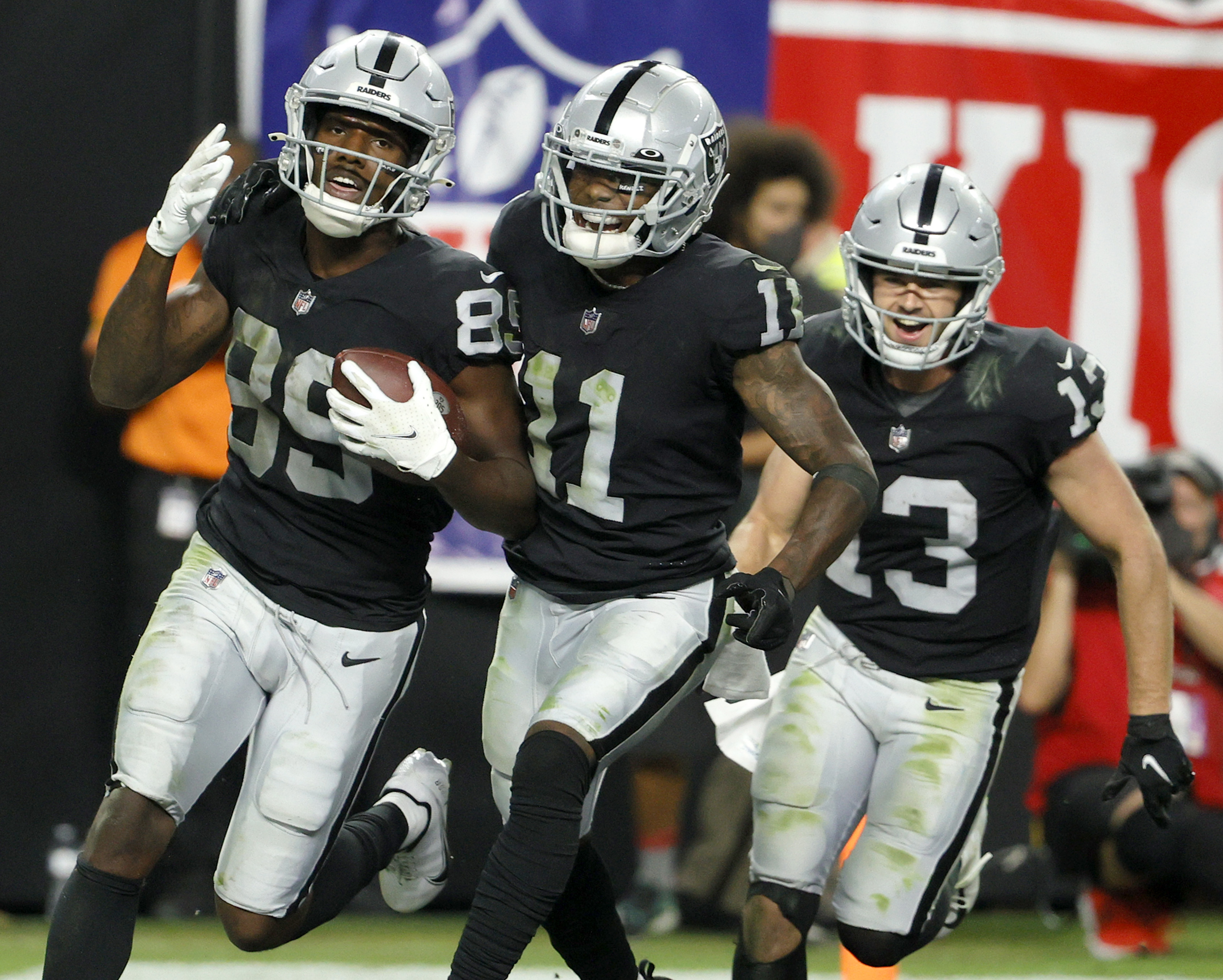 Bryan Edwards of the Las Vegas Raiders celebrates with Henry Ruggs III and Hunter Renfrow after scoring a touchdown that was called down at the 1-yard line after a review during overtime of their game against the Baltimore Ravens at Allegiant Stadium on September 13, 2021 in Las Vegas, Nevada. The Raiders defeated the Ravens 33-27 in overtime.
