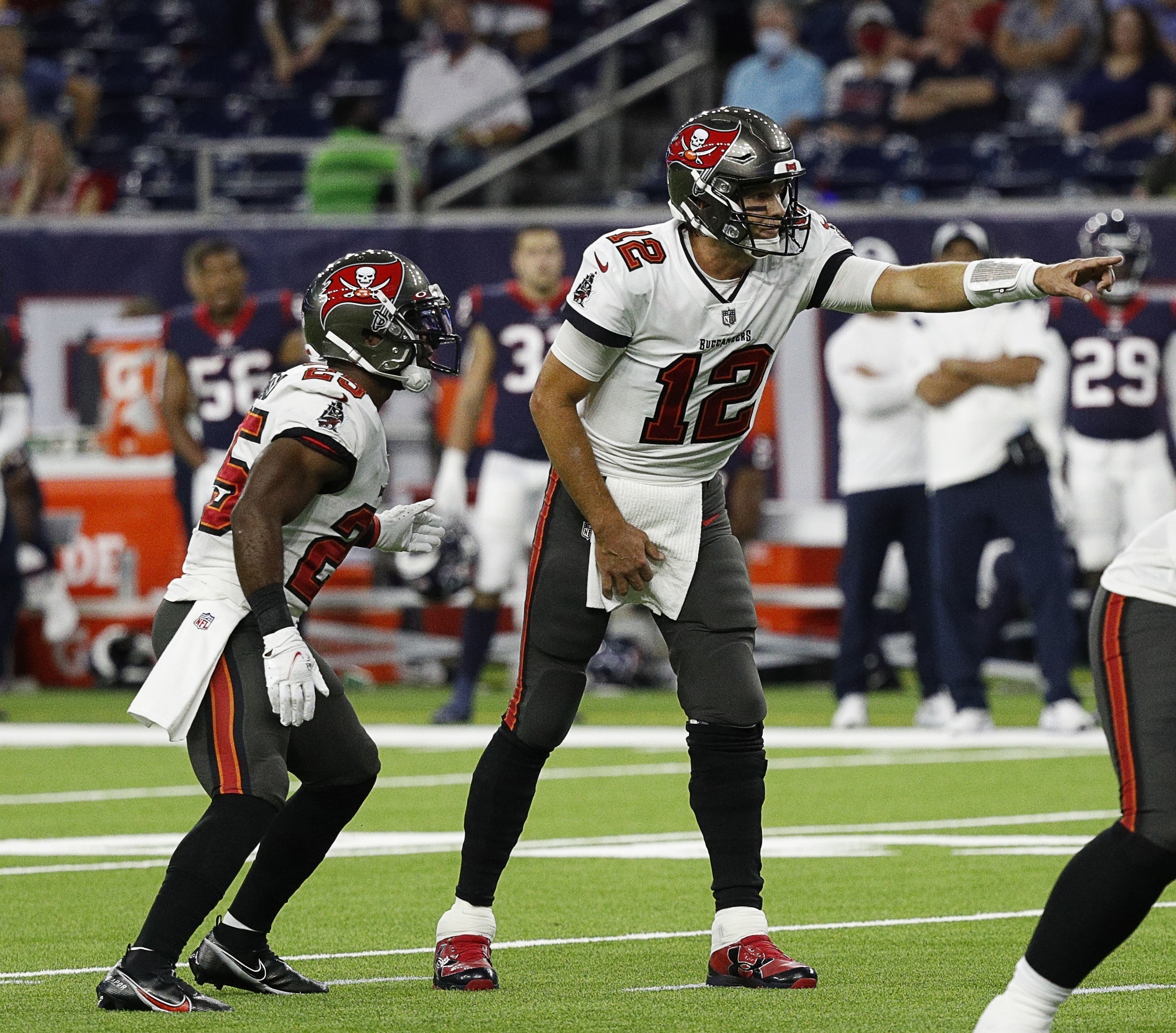 Tom Brady #12 of the Tampa Bay Buccaneers points out the defense as Giovani Bernard #25 goes in motion against the Houston Texans during a NFL preseason game at NRG Stadium on August 28, 2021 in Houston, Texas.