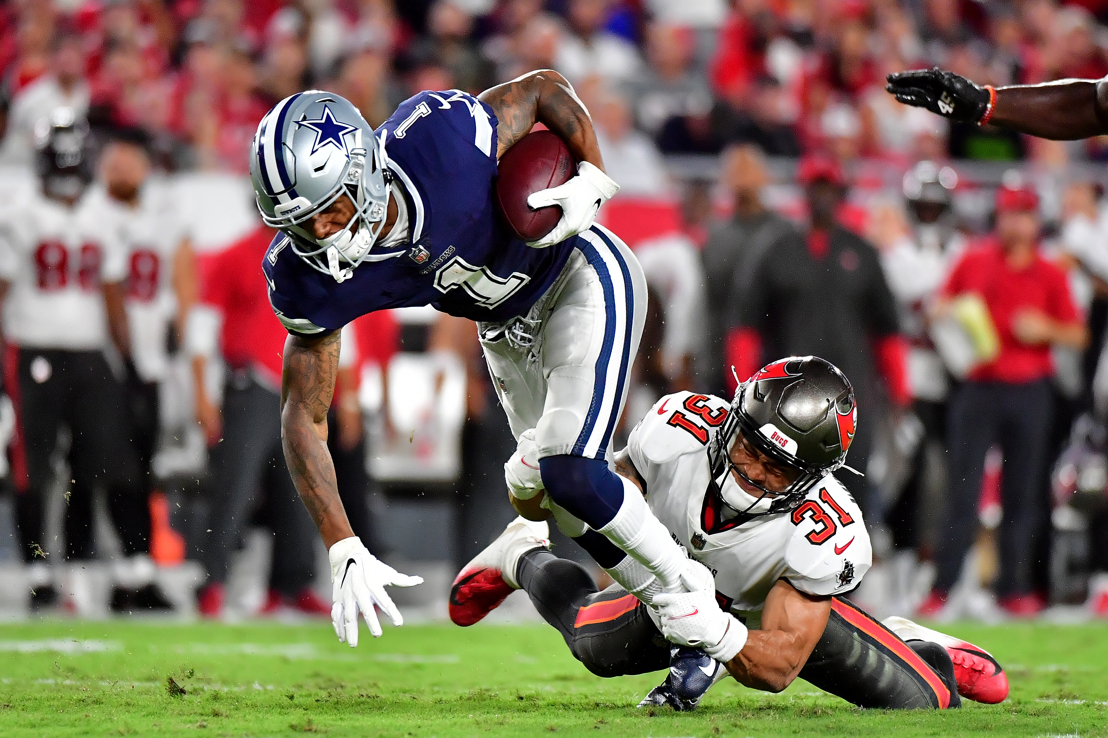 Cedrick Wilson #1 of the Dallas Cowboys carries the ball for a first down against Antoine Winfield Jr. #31 of the Tampa Bay Buccaneers during the second quarter at Raymond James Stadium on September 09, 2021 in Tampa, Florida.