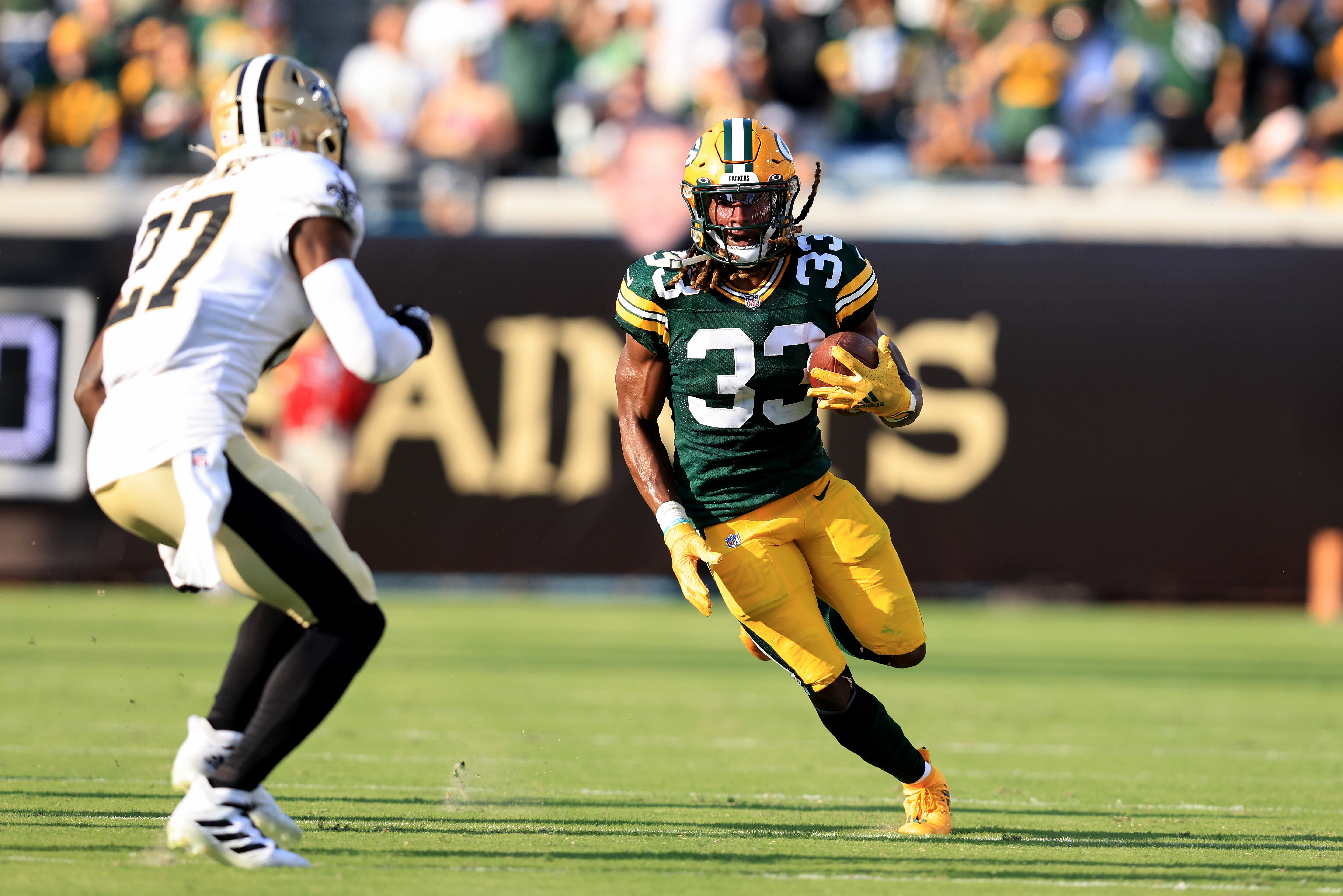 Aaron Jones #33 of the Green Bay Packers rushes for yardage during the game against the New Orleans Saints at TIAA Bank Field on September 12, 2021 in Jacksonville, Florida.