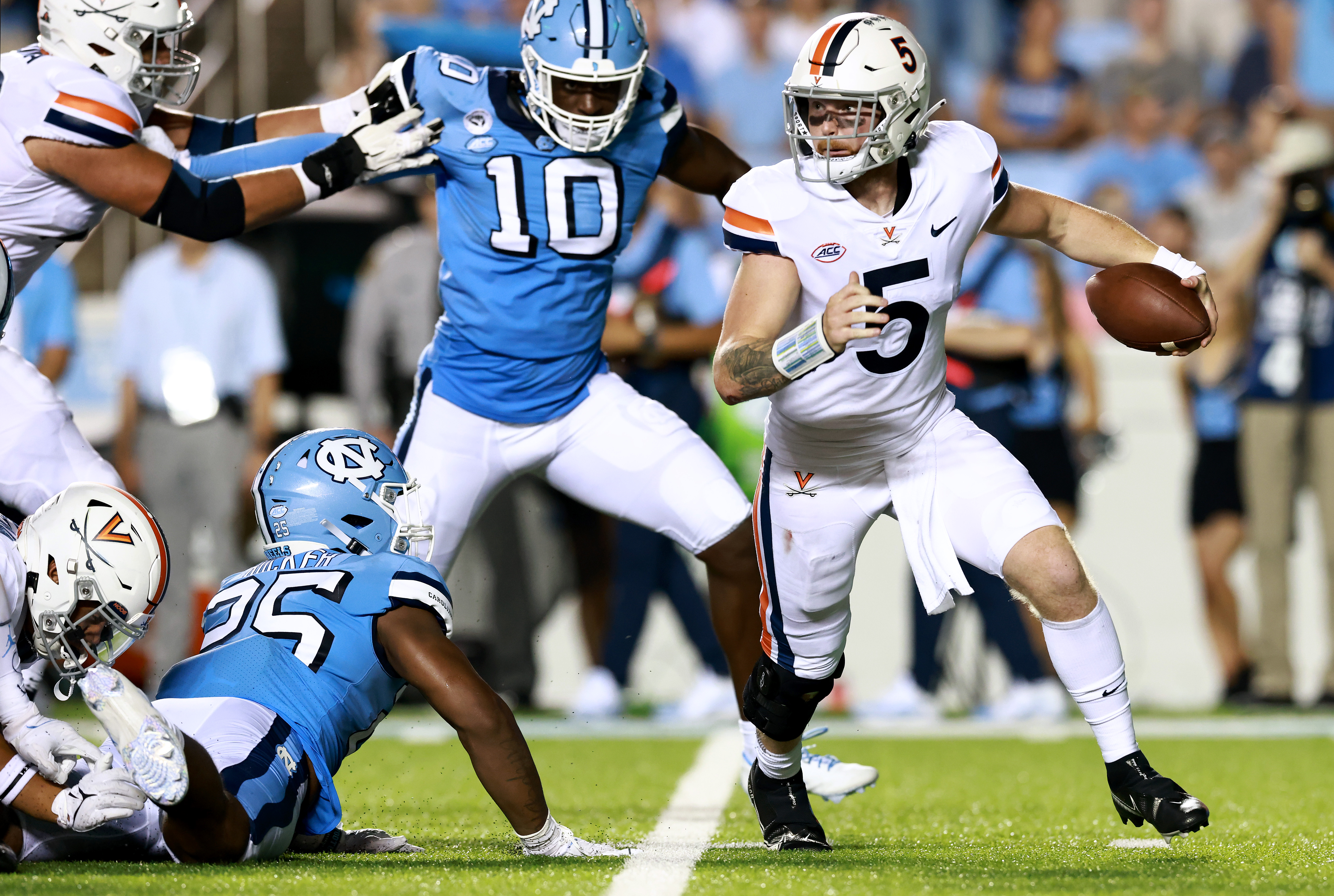 Brennan Armstrong #5 of the Virginia Cavaliers rolls out under pressure from Kaimon Rucker #25 and Desmond Evans #10 of the North Carolina Tar Heels during the first half of their game at Kenan Memorial Stadium on September 18, 2021 in Chapel Hill, North Carolina.